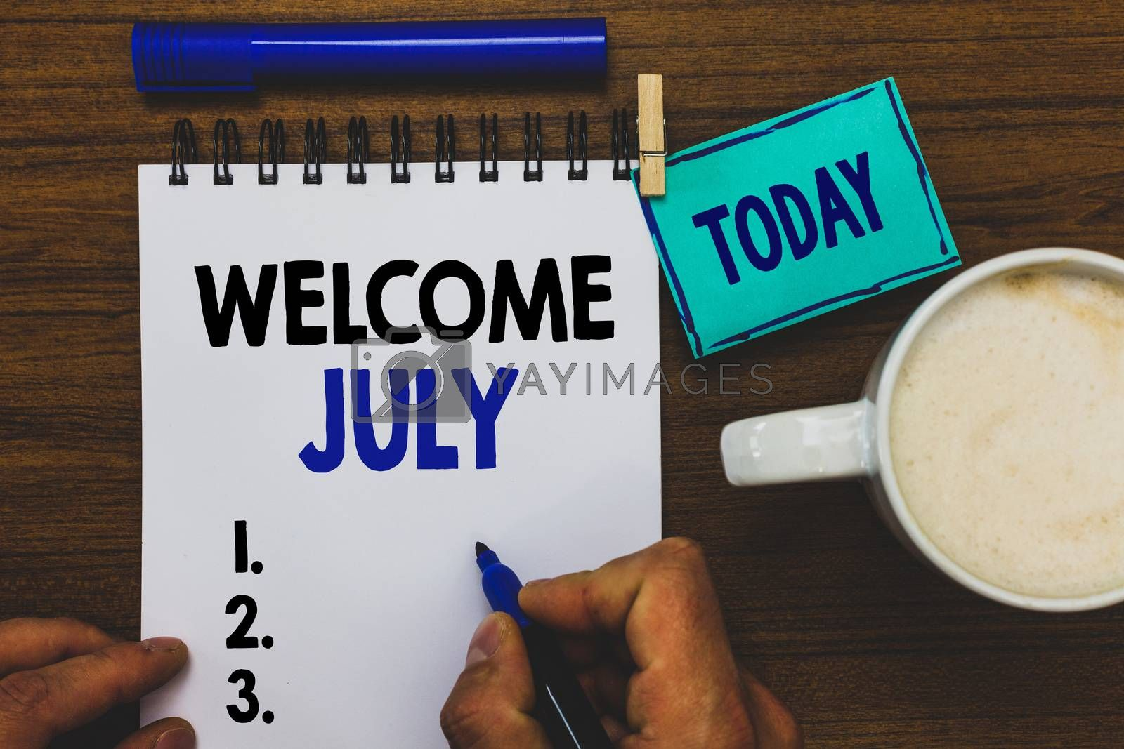 Royalty free image of Conceptual hand writing showing Welcome July. Business photo text Calendar Seventh Month 31days Third Quarter New Season Man holding marker notebook clothepin reminder wooden table coffee. by artursz