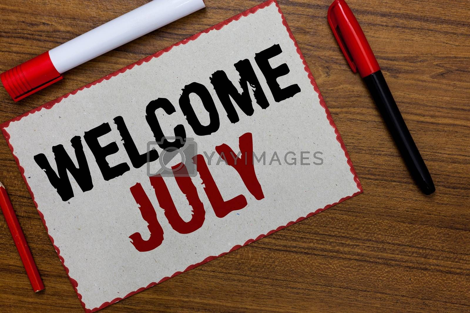 Royalty free image of Text sign showing Welcome July. Conceptual photo Calendar Seventh Month 31days Third Quarter New Season White paper red borders markers wooden background communicating ideas. by artursz