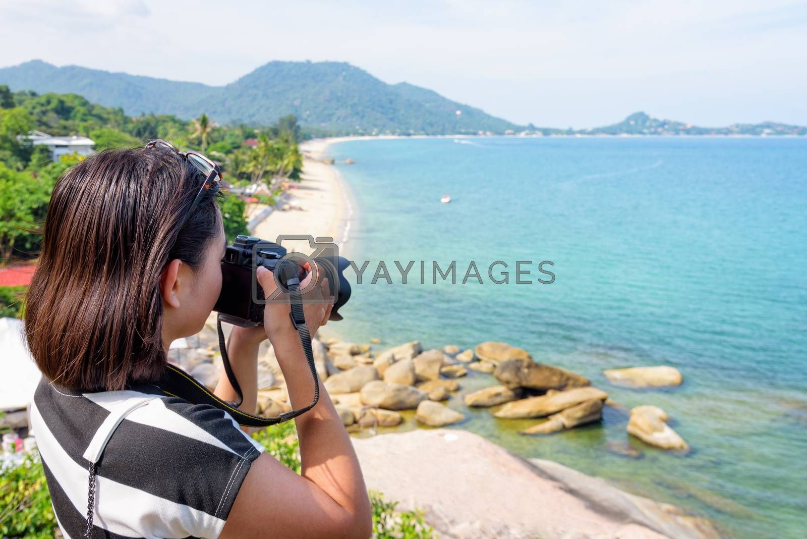 Young woman are using a DSLR camera to photography of the sea and beautiful nature landscape on Lamai beach viewpoint under the summer sky at Koh Samui island, Surat Thani, Thailand
