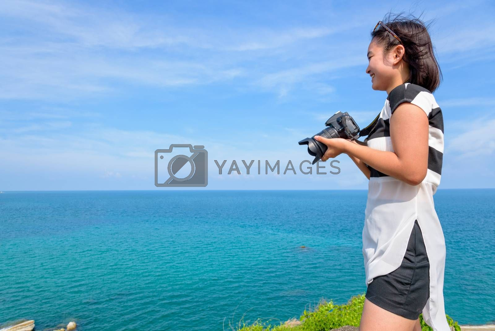 Teenage girl is holding a dslr camera smiling happily on the top of the island with the beautiful natural landscape of the blue sea and the summer sky as the background.