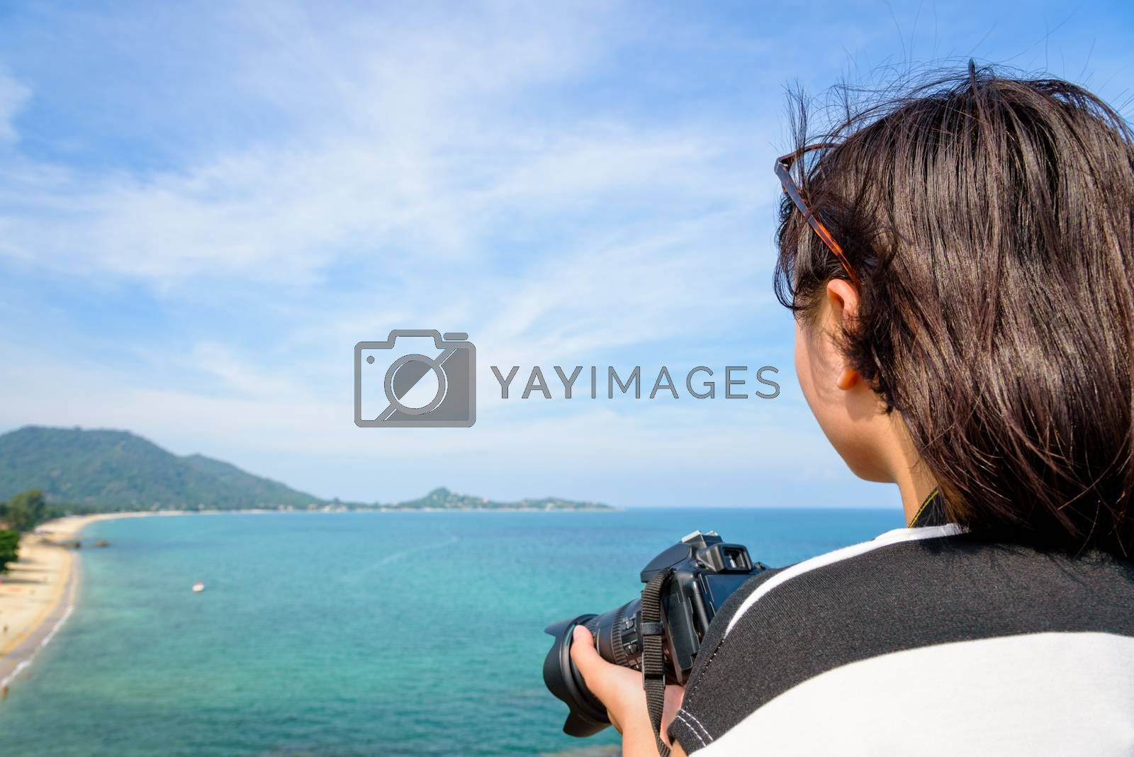 Teenage girl is holding a dslr camera on high and beautiful nature landscape of the blue sea on Lamai beach hight viewpoint during summer travel at Koh Samui island, Surat Thani, Thailand