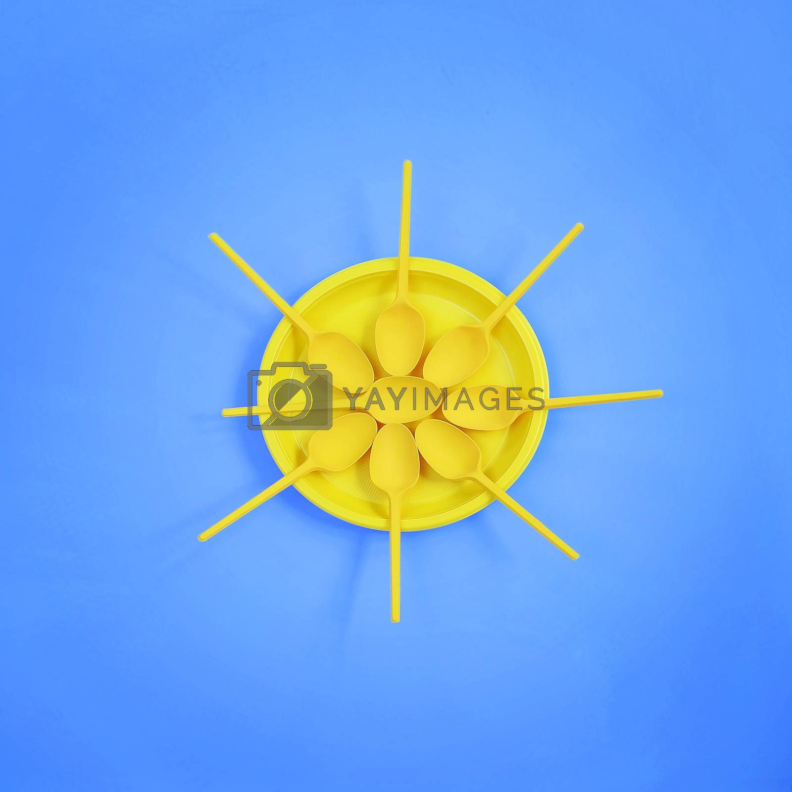 A yellow plastic plate and spoons lay around it on a bright blue background. The concept of a holiday, picnic
