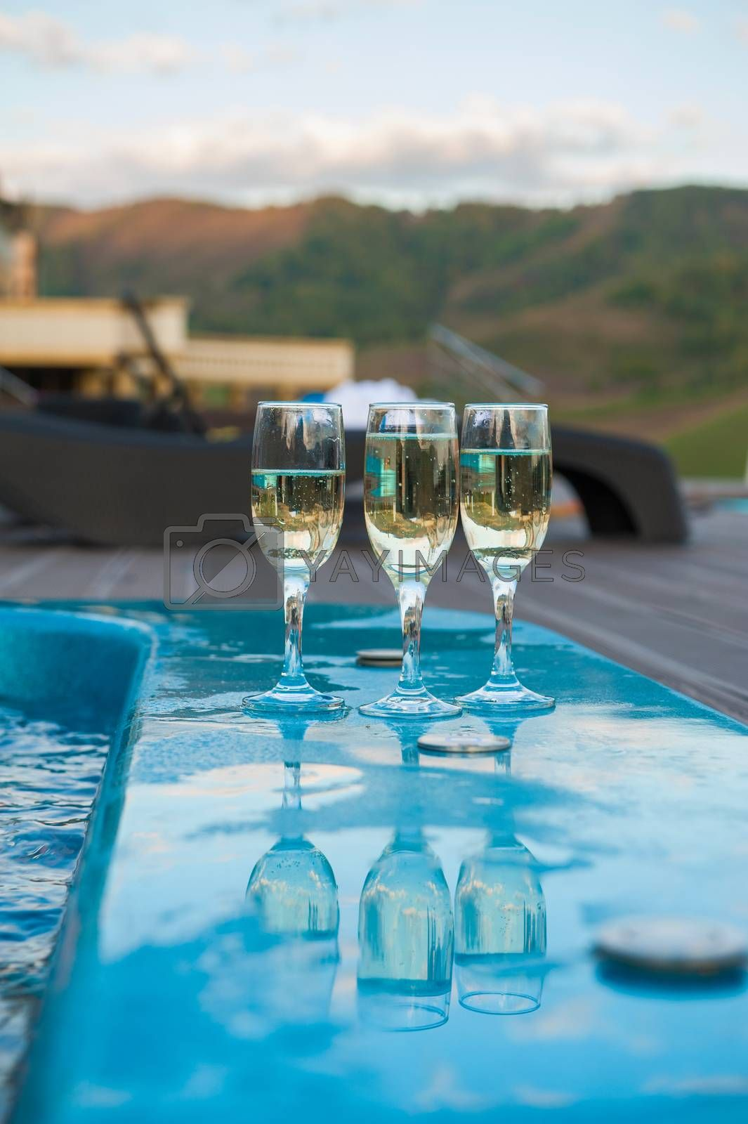 Three glass of cool champagne wine outdoor in a restaurant pool, terrace in mountain
