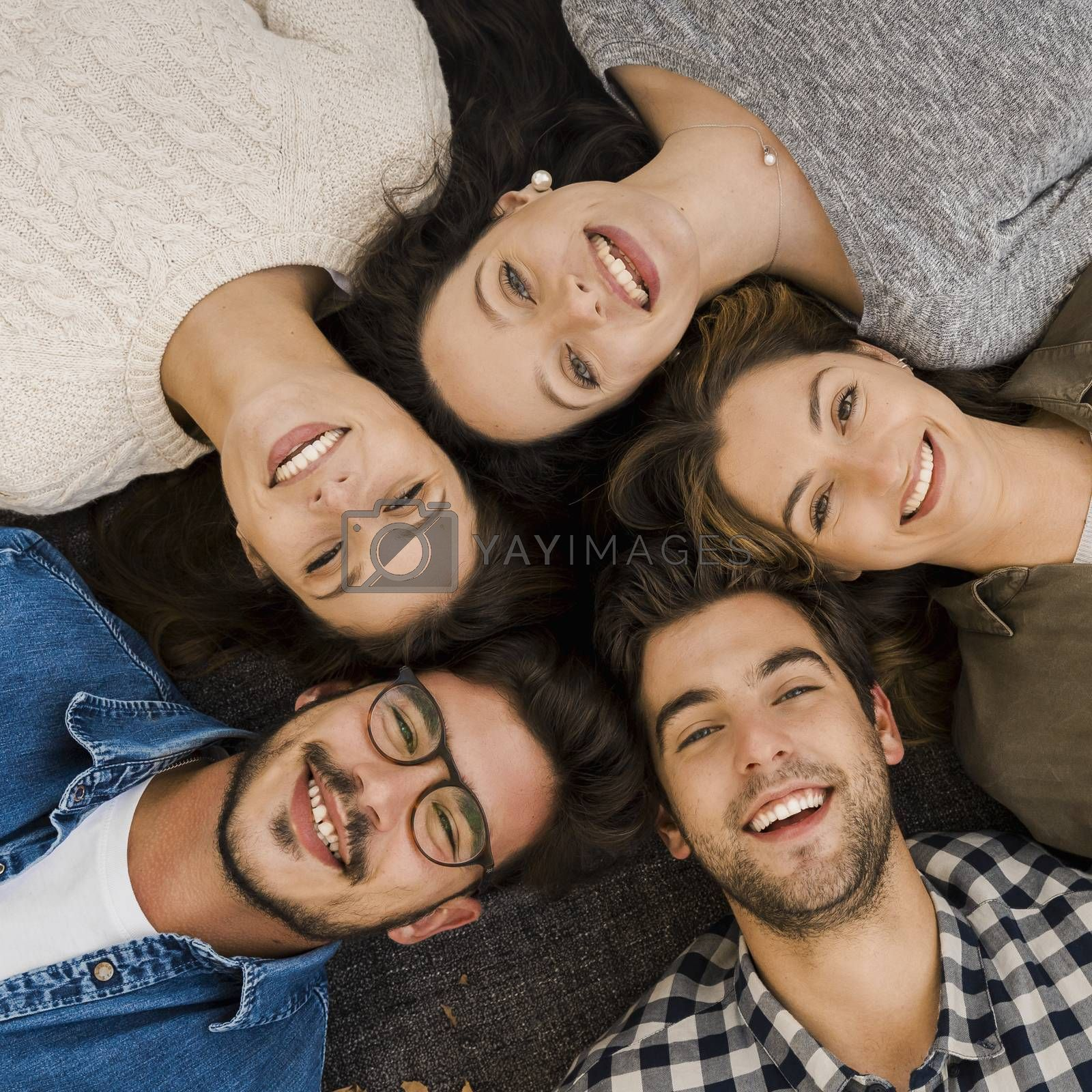 Top view of a group of friends lying on floor and looking at camera