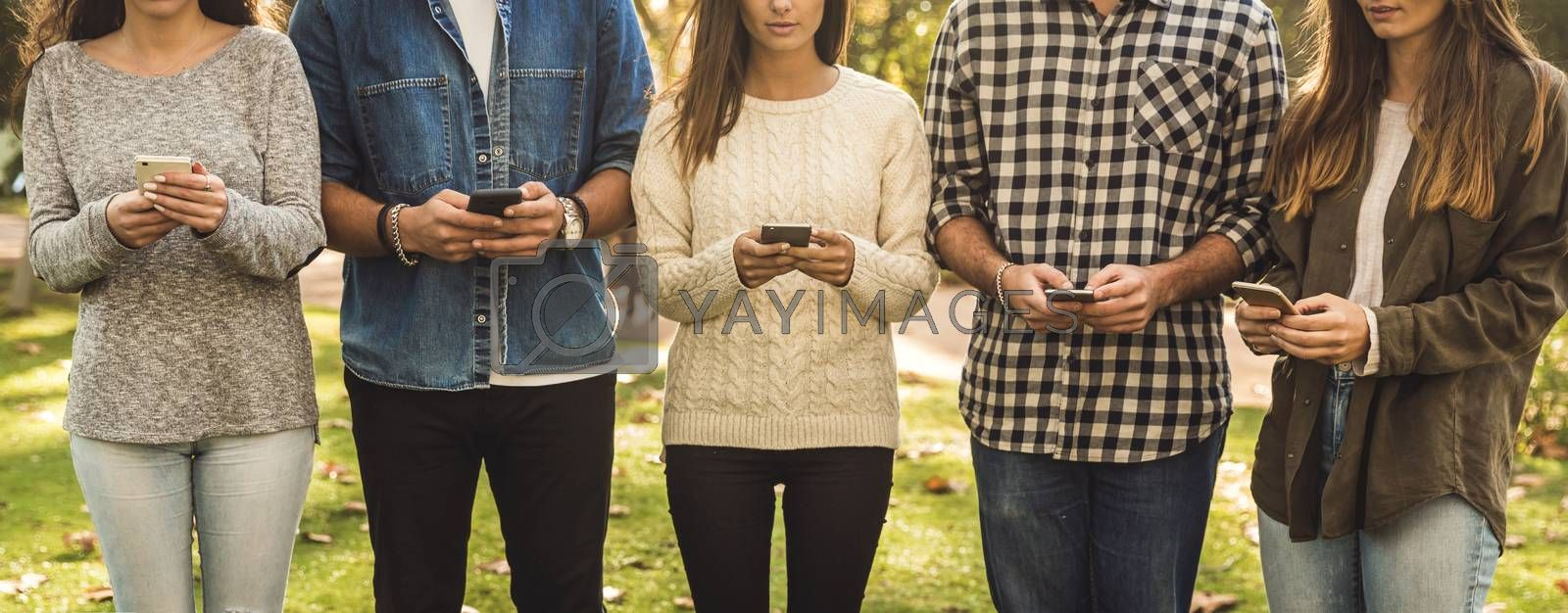 Group of friends distracted with social networks on their phones