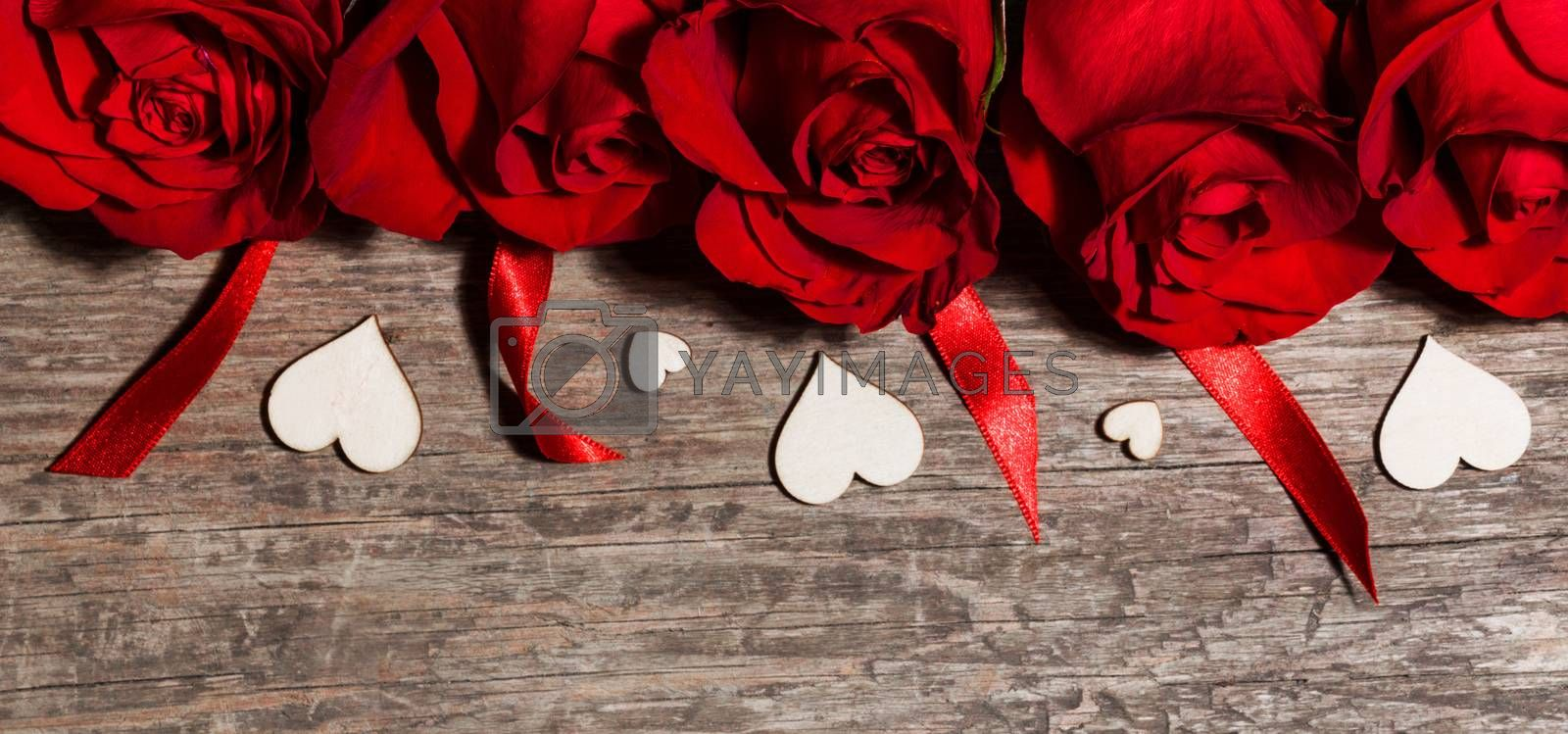 Roses ribbons and wooden hearts on wooden background, Valentines day