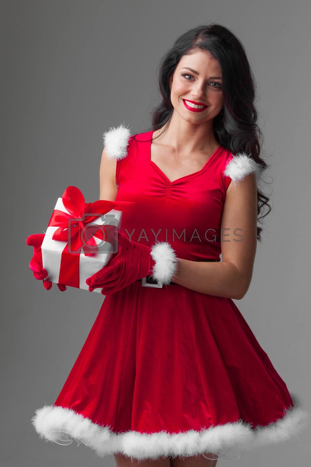 Beautiful young woman in Santa dress celebrating Christmas holding gift box
