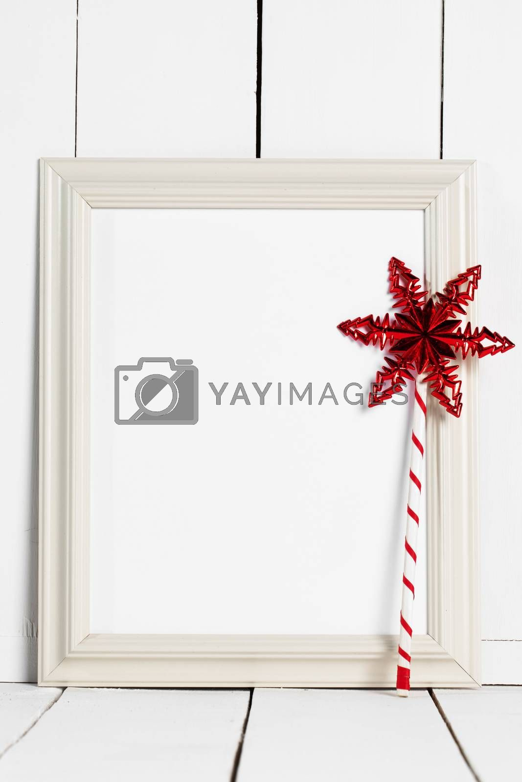 Vintage white wooden picture frame with blank white copy space and red star magic wand