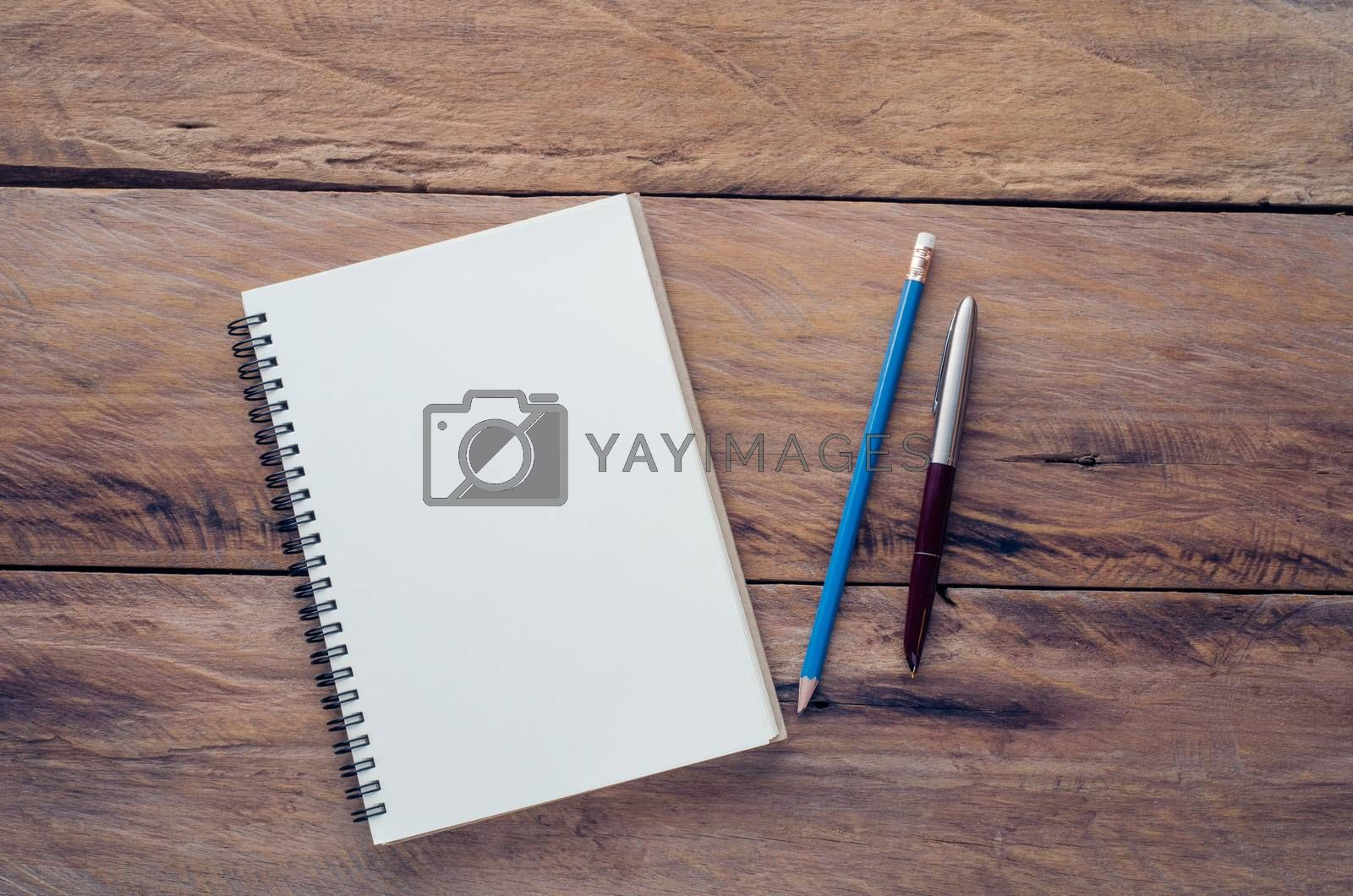 blank notebook with pencil and pen on wooden table - still life