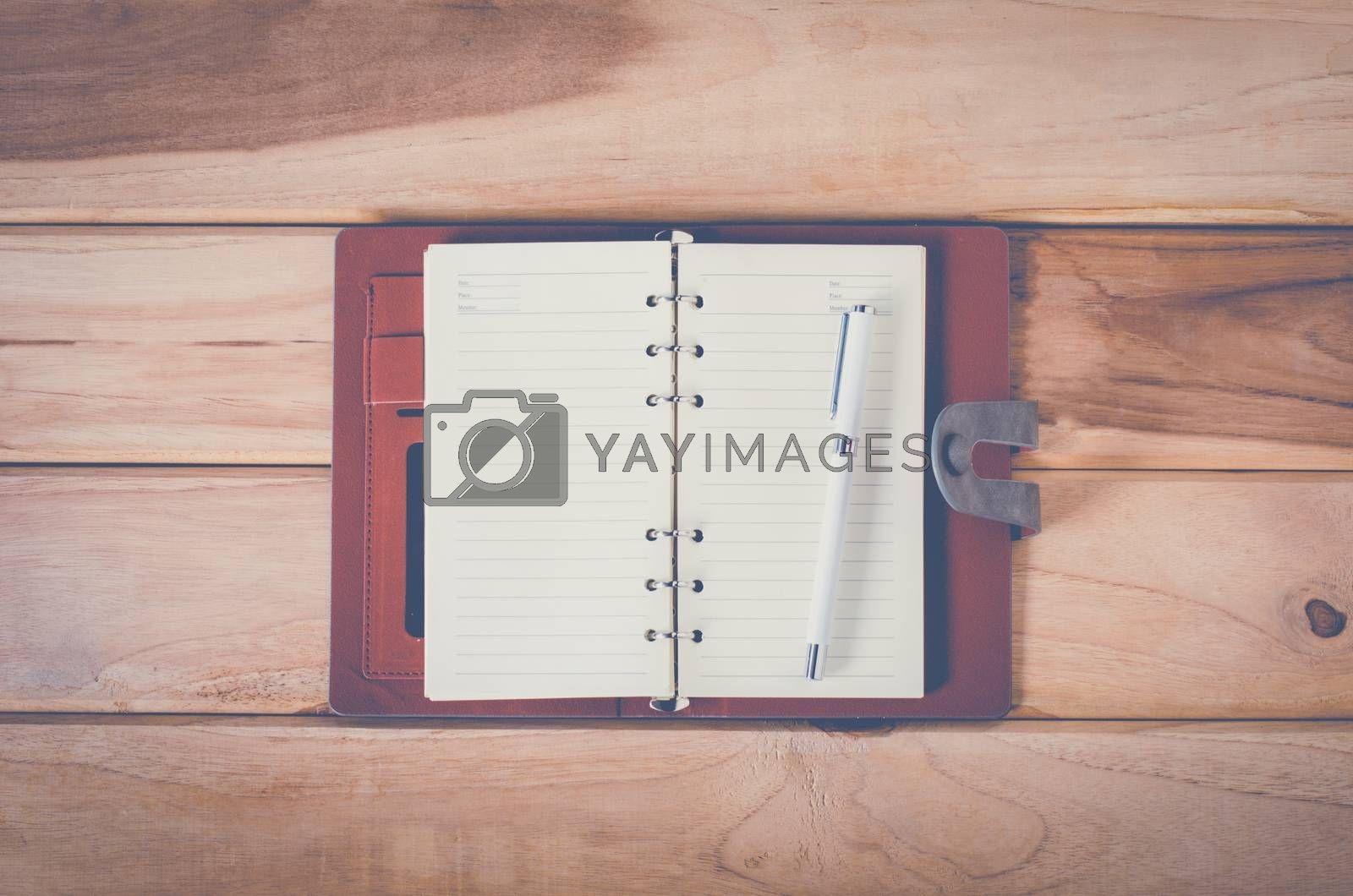 blank notebook with pen on wooden table