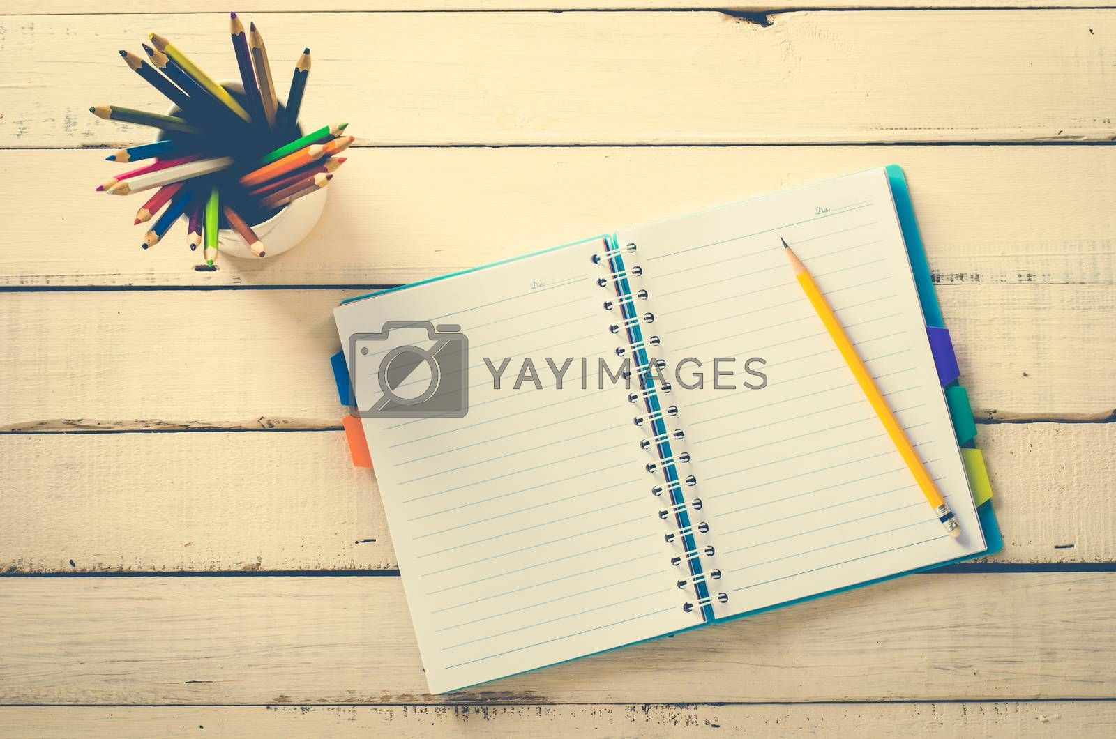 Color pencil and notebook on wood table rough