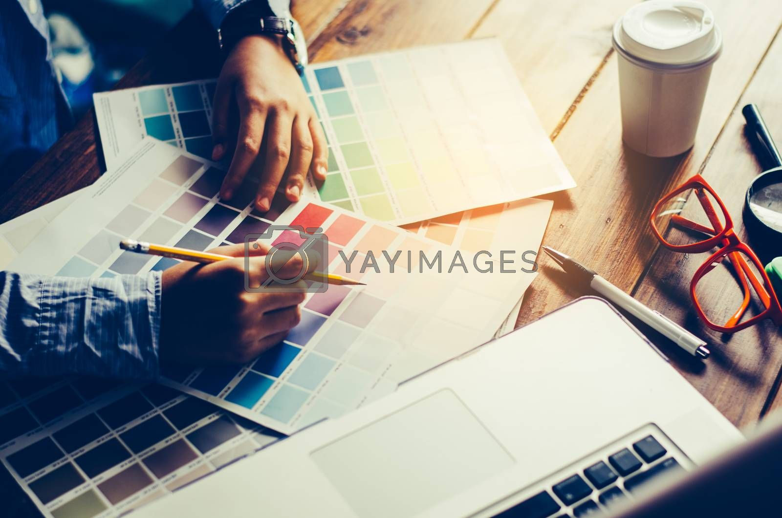 Graphic designer architects who work with laptops and color comparison tables for design work.