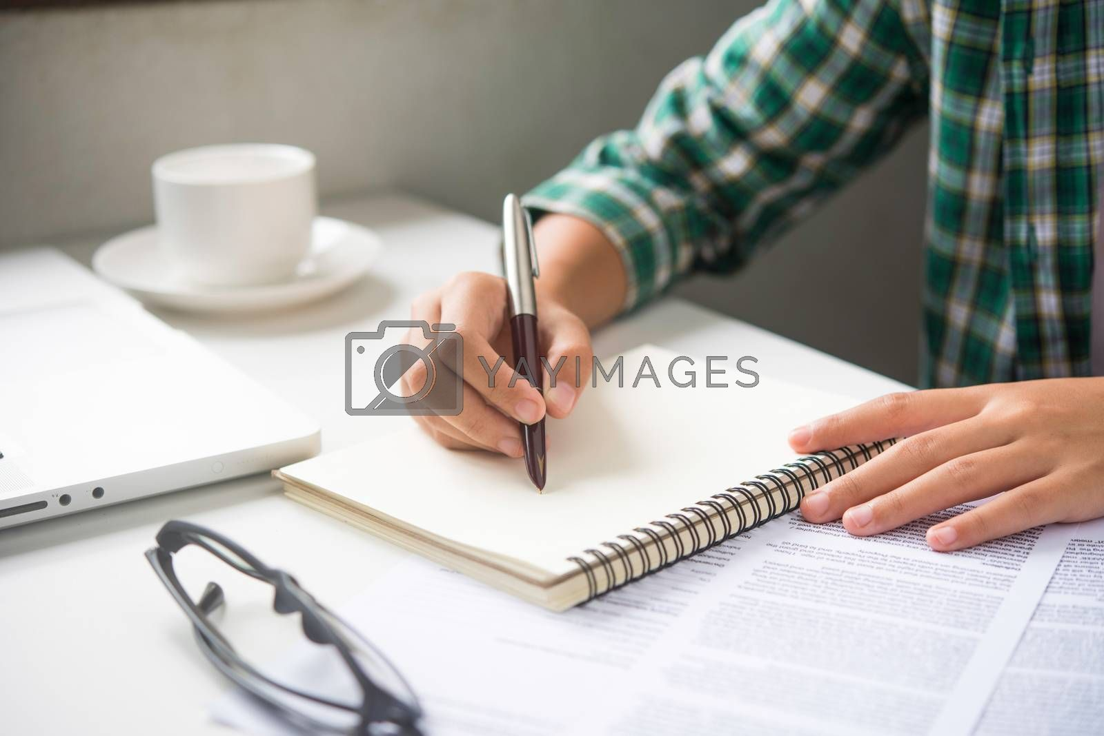 Close up of woman hands writing inon paper placed on wooden in office