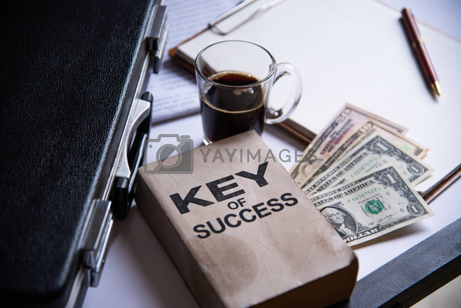 Black coffee and dollar is placed on a desk with office equipment and placed.