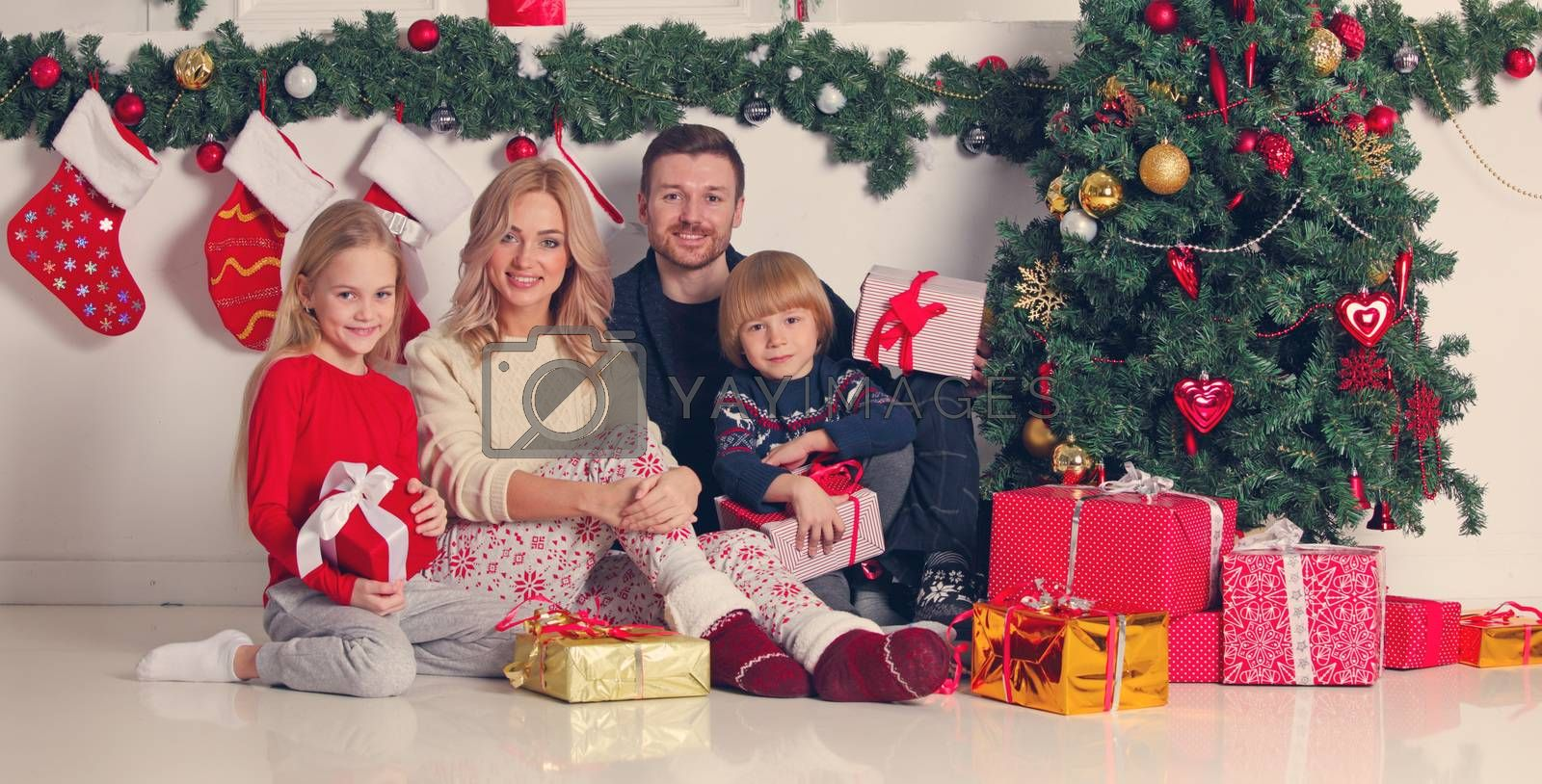 Cheerful family with Christmas gifts sitting near decorated Christmas tree