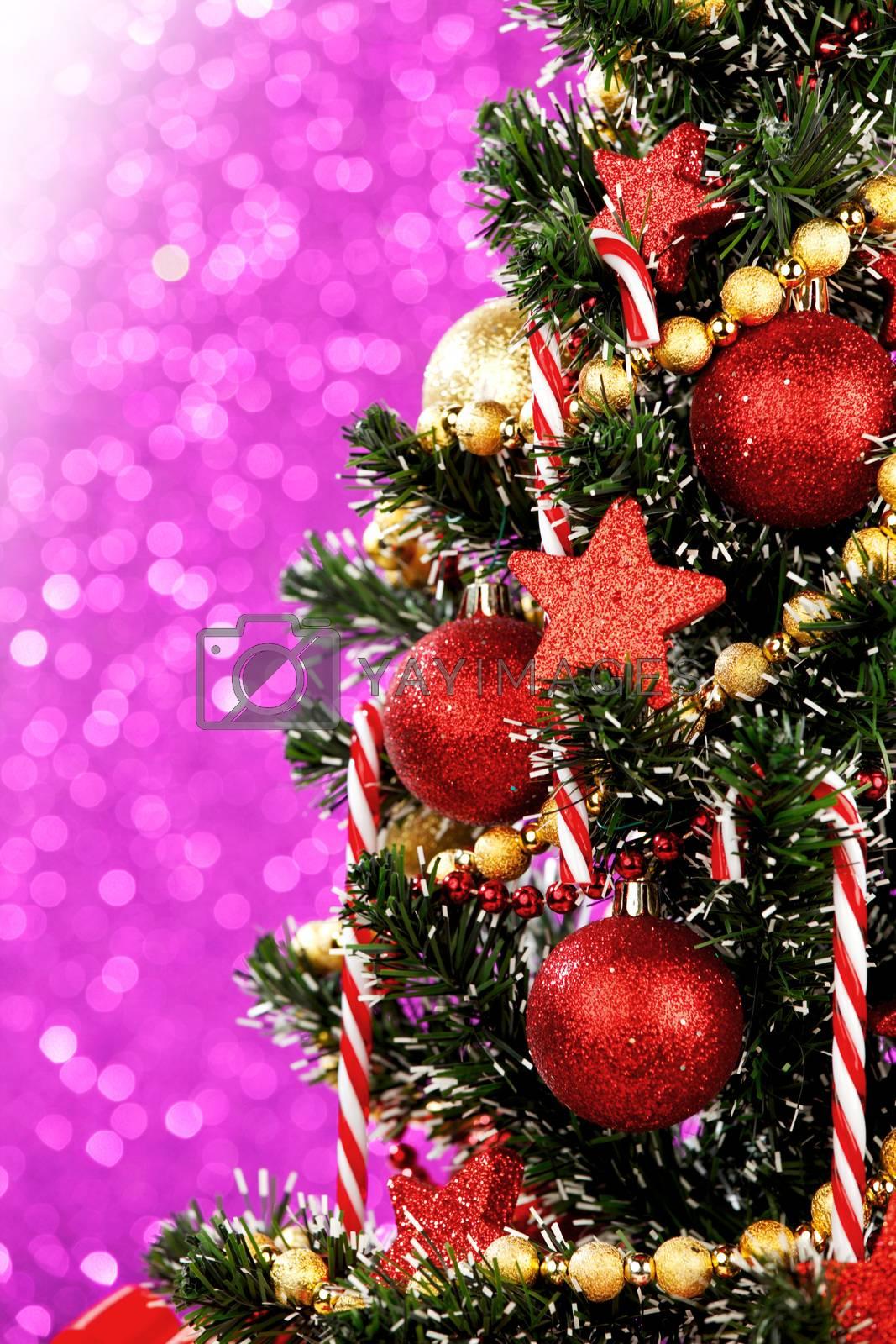 Beautiful decorated christmas tree on glitter purple background