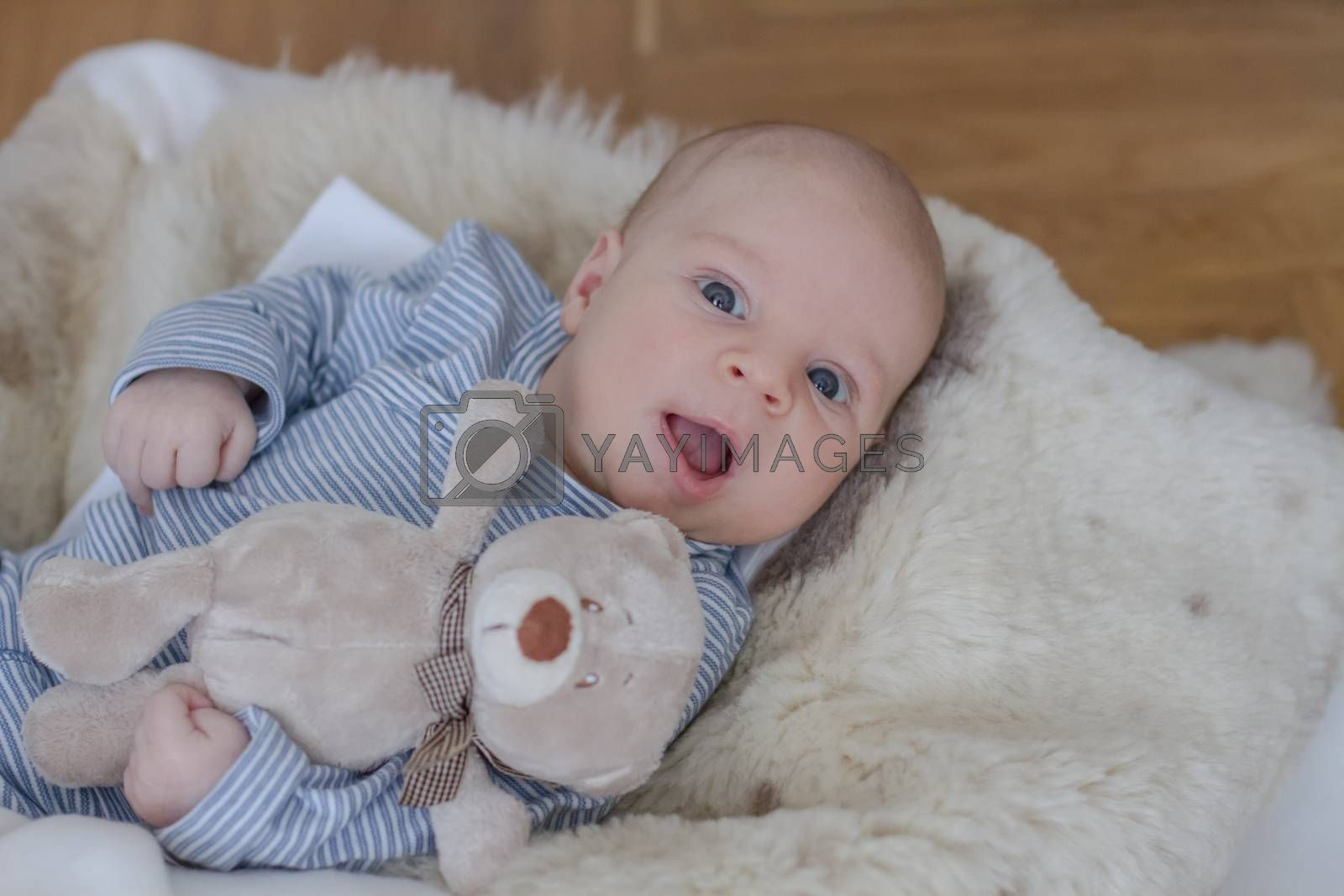 Cute one month old baby boy lying with teddy bear
