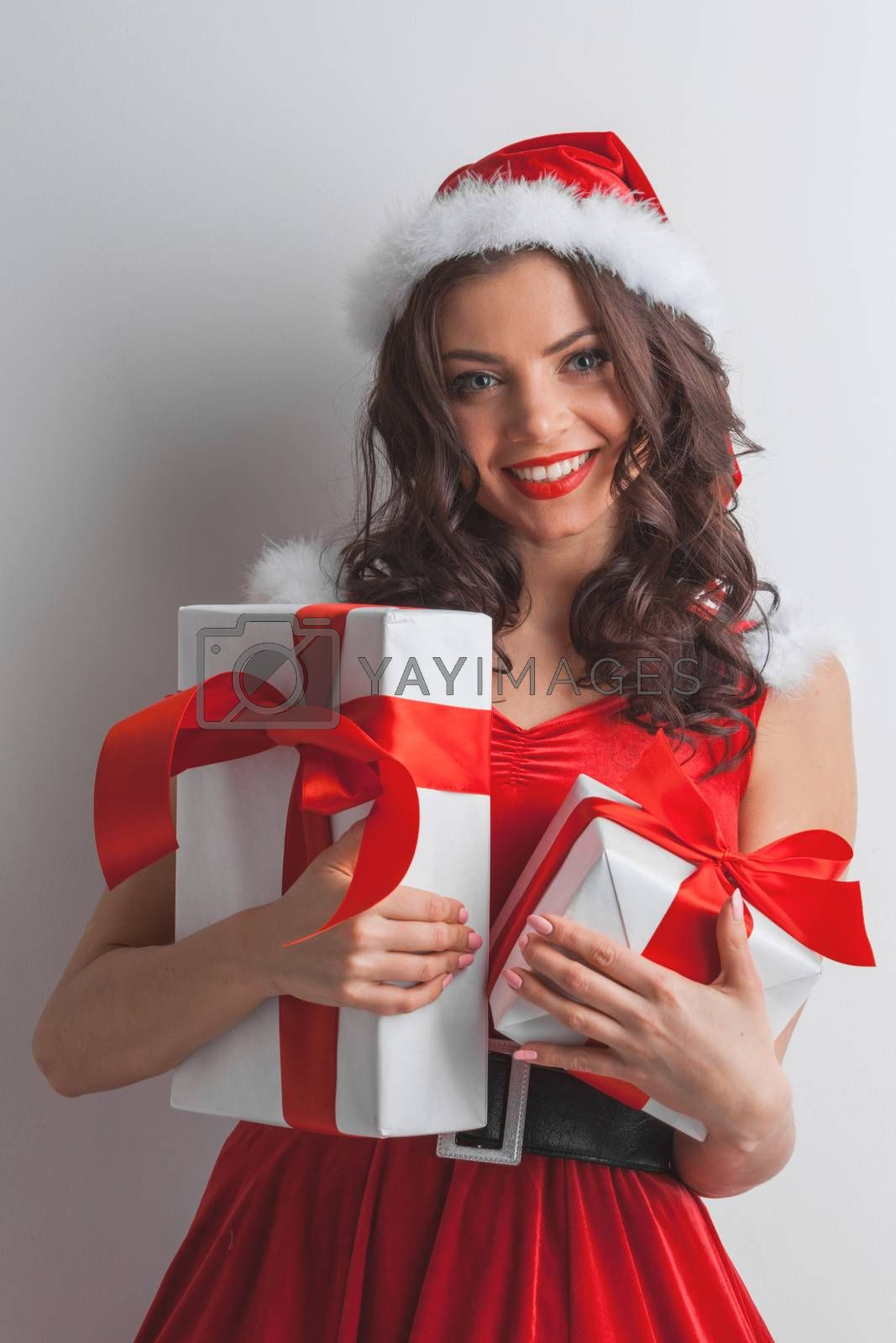 Beautiful young woman in Santa dress celebrating Christmas holding gift boxes