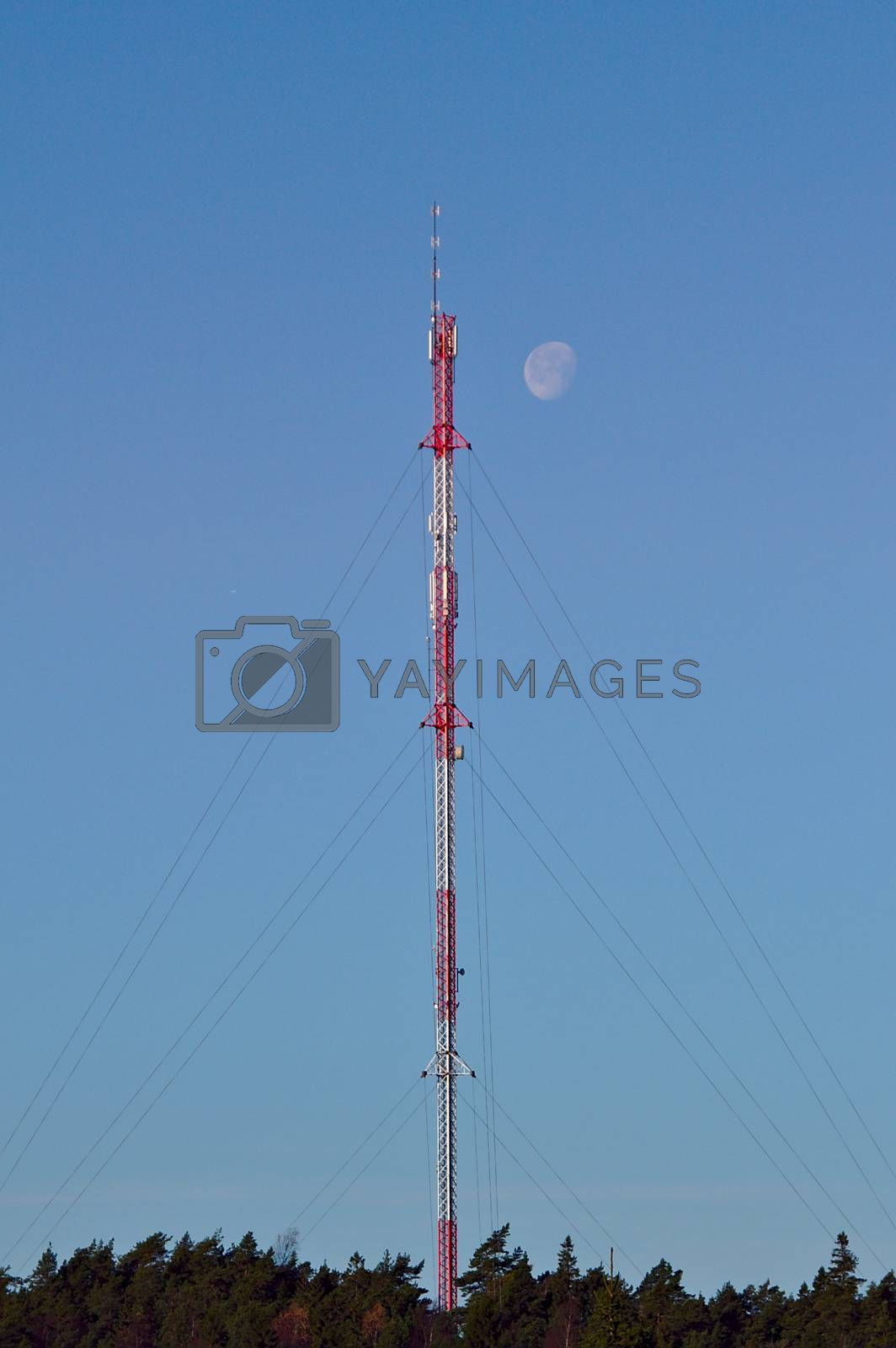 High red and white cellular tower at daytime with moon shining next to the top of the tower.