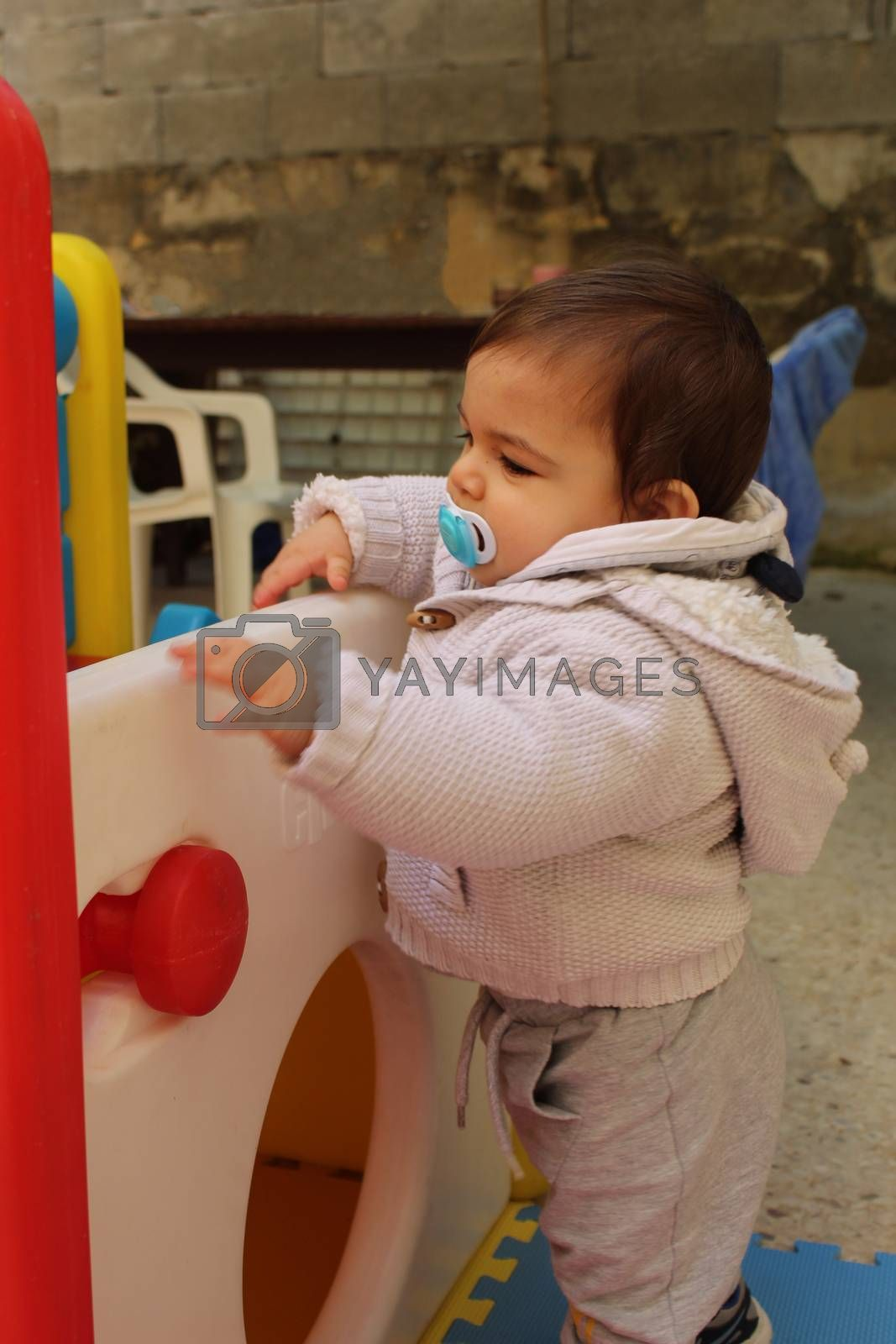Baby boy playing with plastick house slide for toddlers