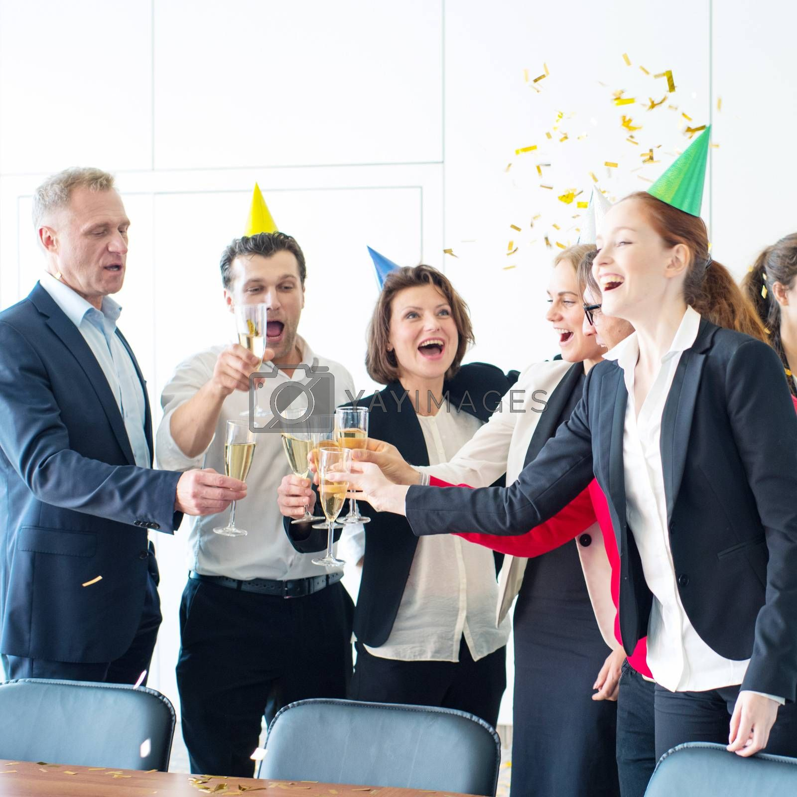 Business people celebrating victory at office party holding glasses of champagne