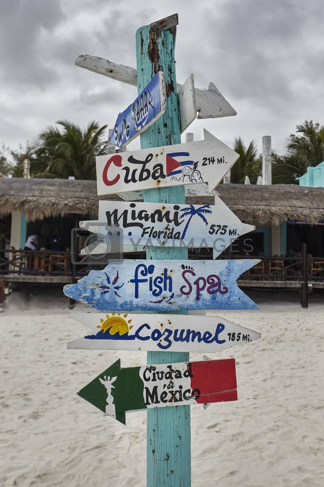 Sign with wooden arrows and blue, containing indications for cuba, florida, cozumel, ciuda de mexico and fish spa