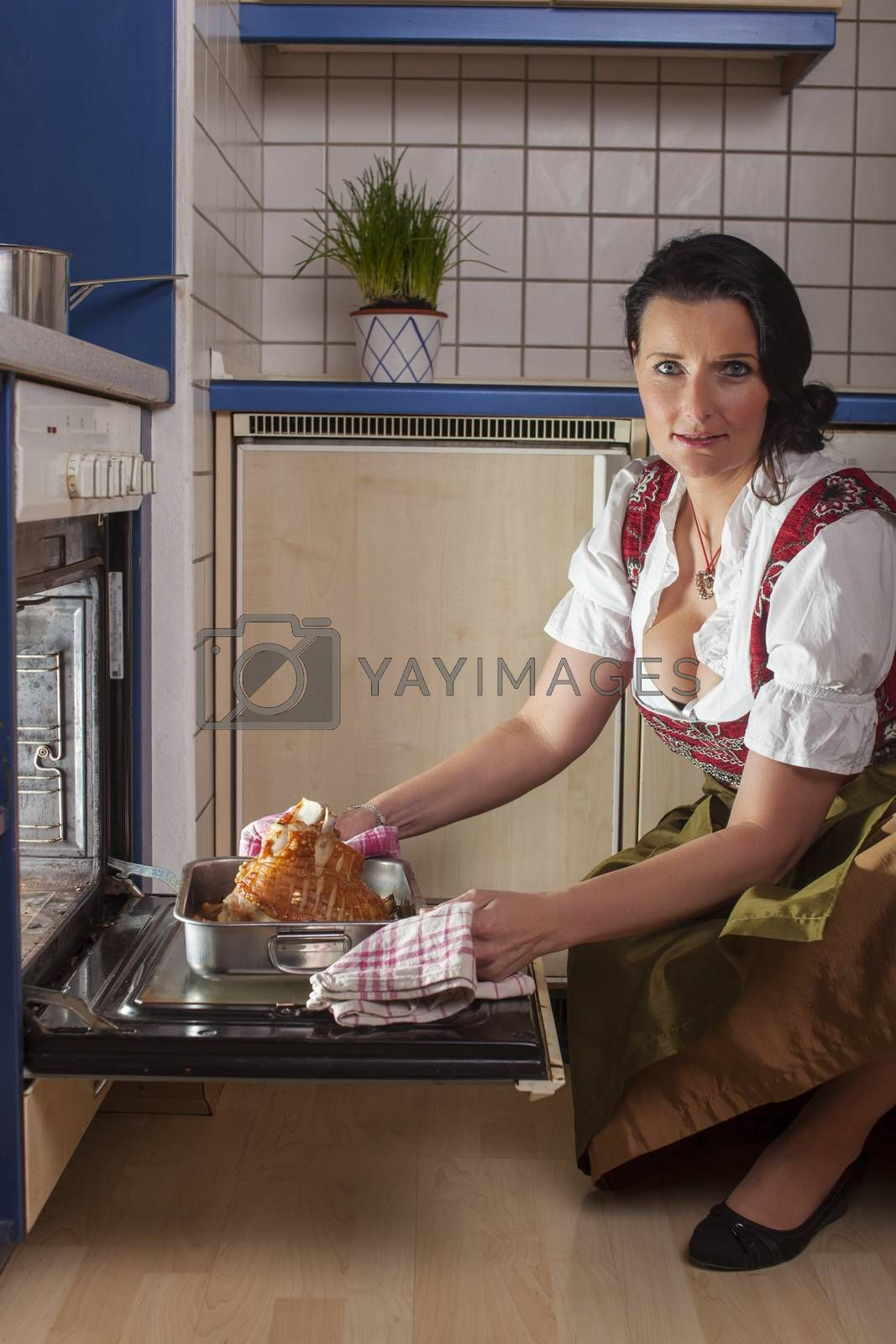 bavarian woman in a dirndl cooking