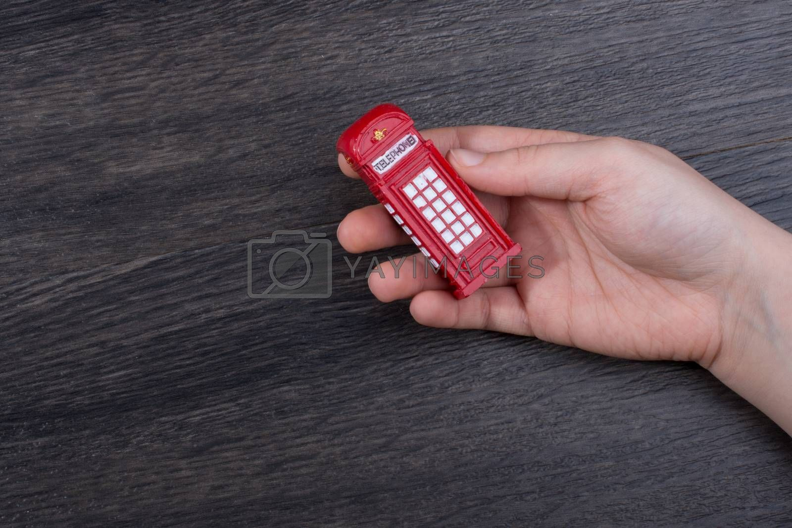 Hand holding a phone booth on a brown background