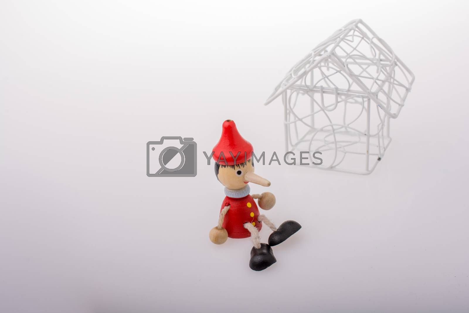 Pinocchio is sitting beside a model house