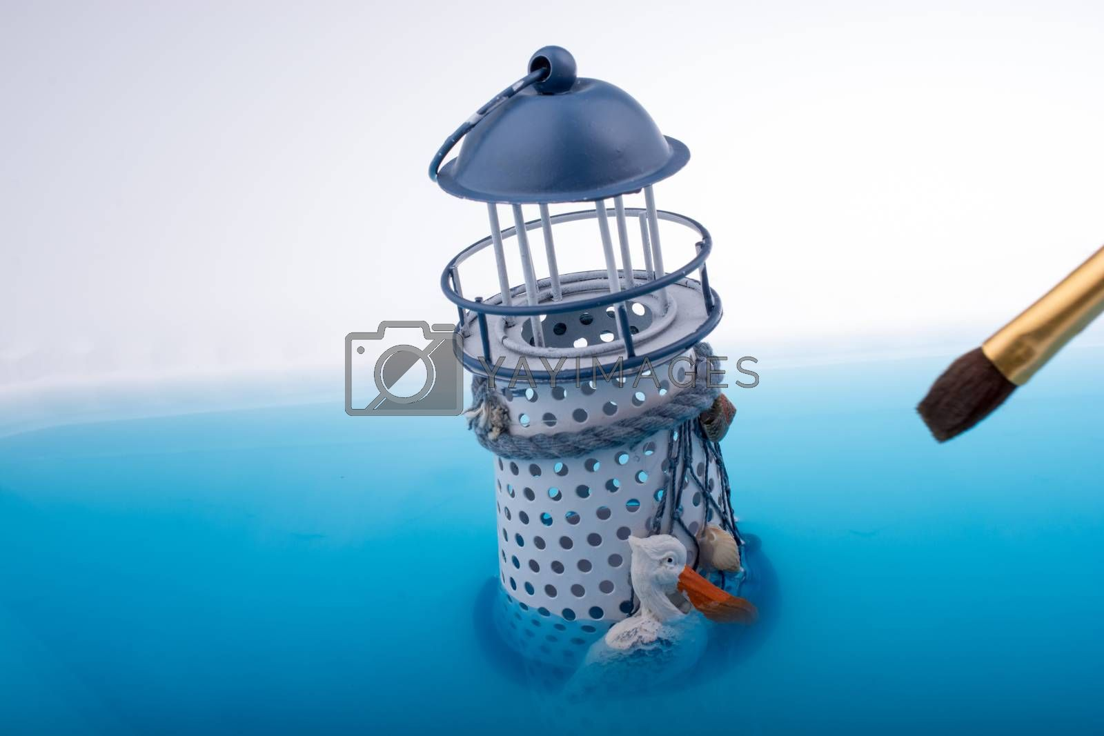 Painting brush and little model lighthouse  placed in blue water