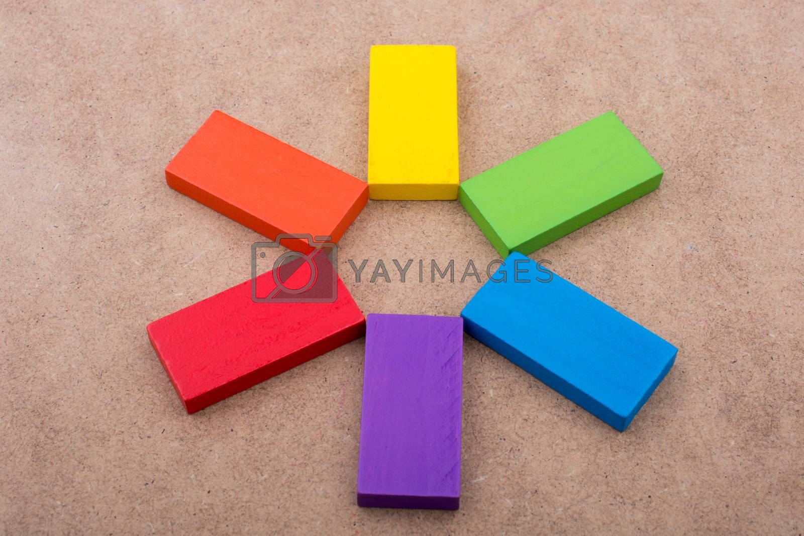 Hand holding one of the wooden blocks of various colors