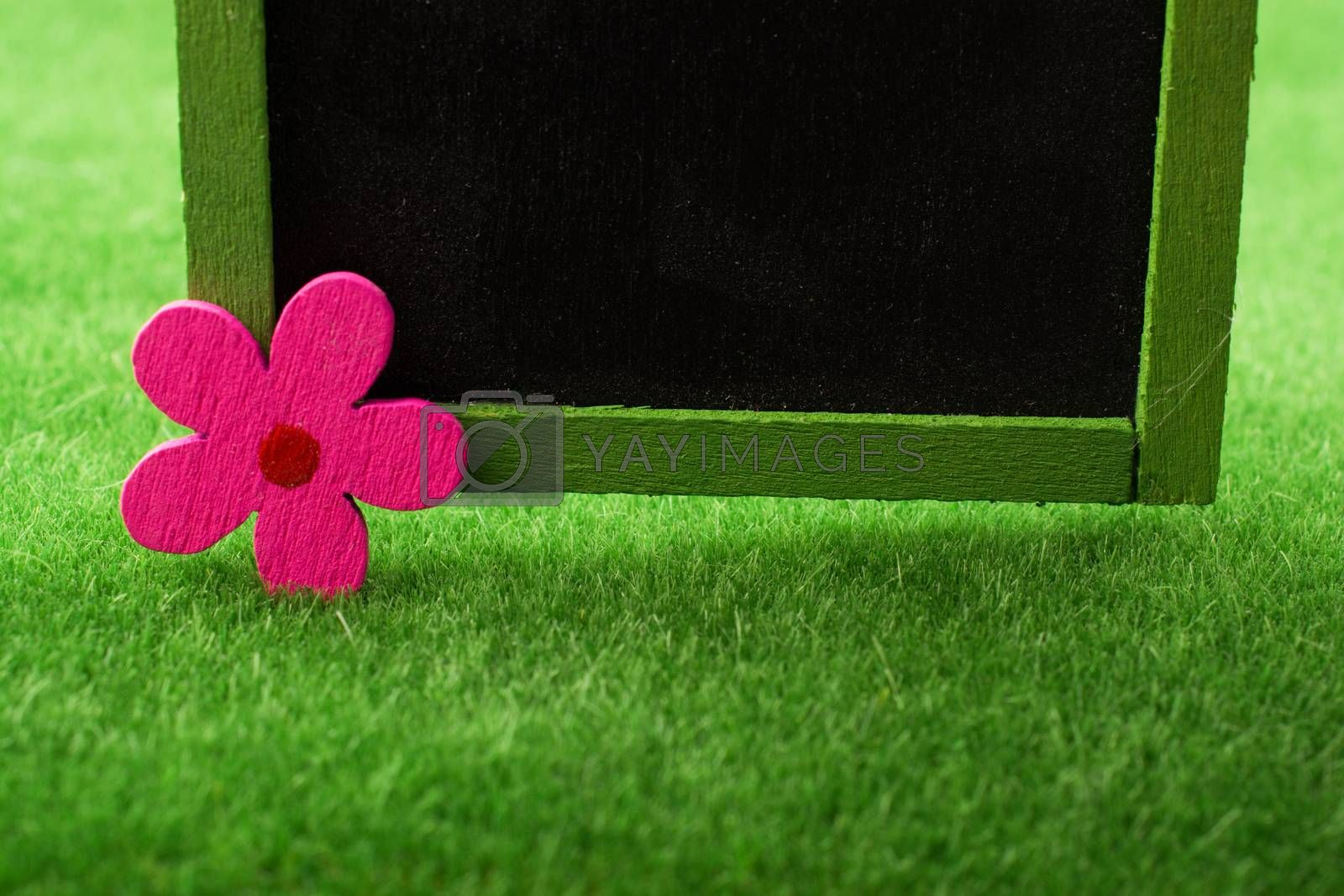 Writing board with a flower is placed on green grass