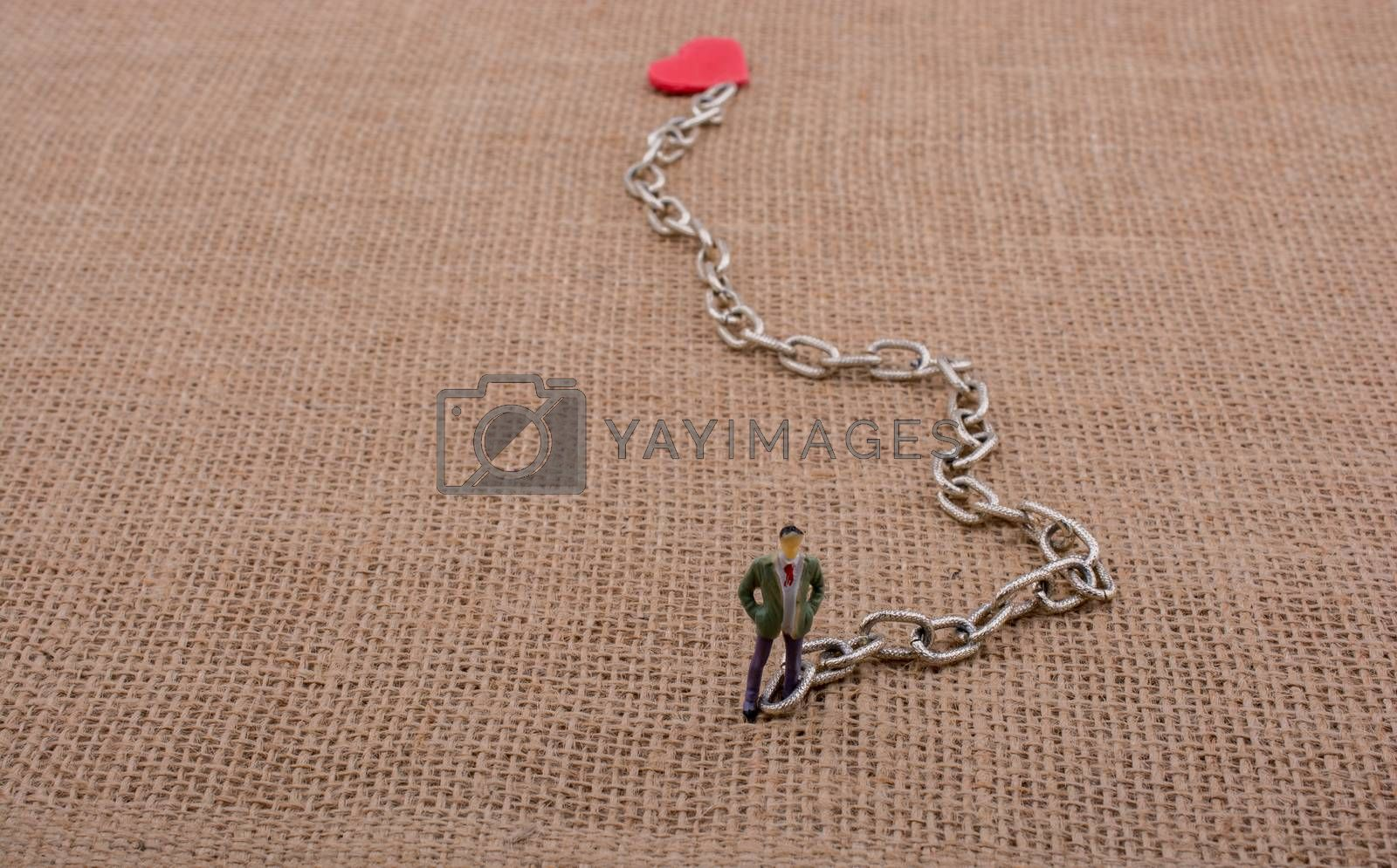 Heart shaped object attached to a man figurine on canvas