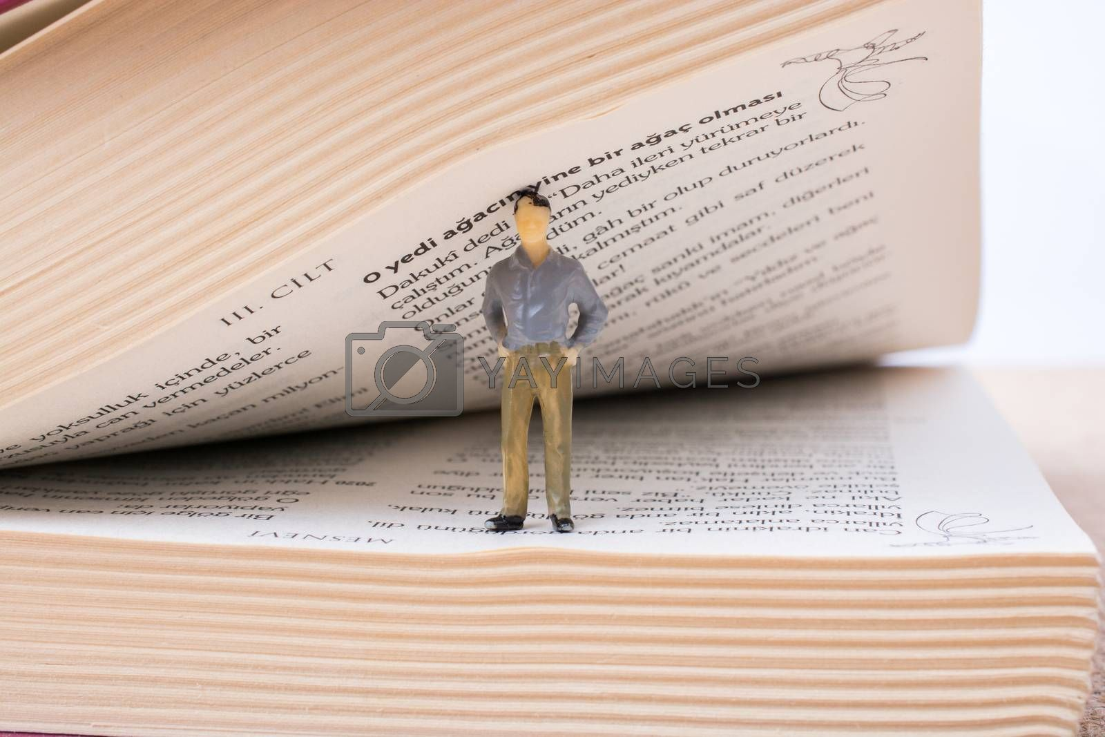 Man figurine standing inside the pages of the  book