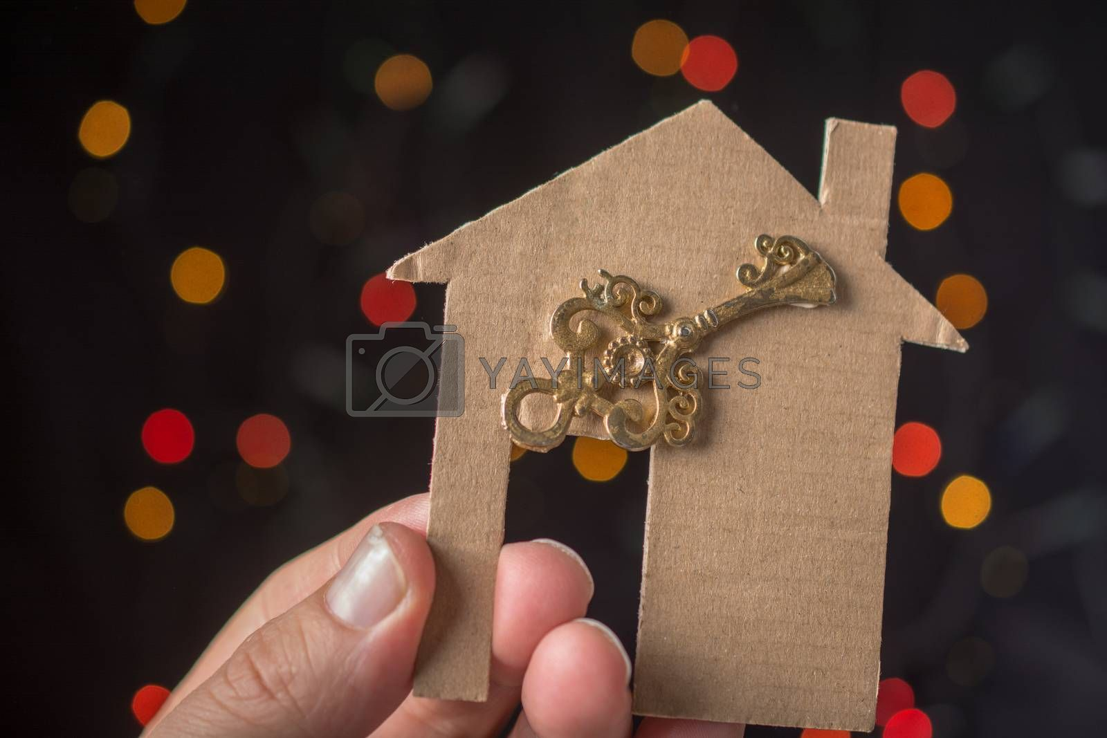 Key on paper house on a bokeh light background