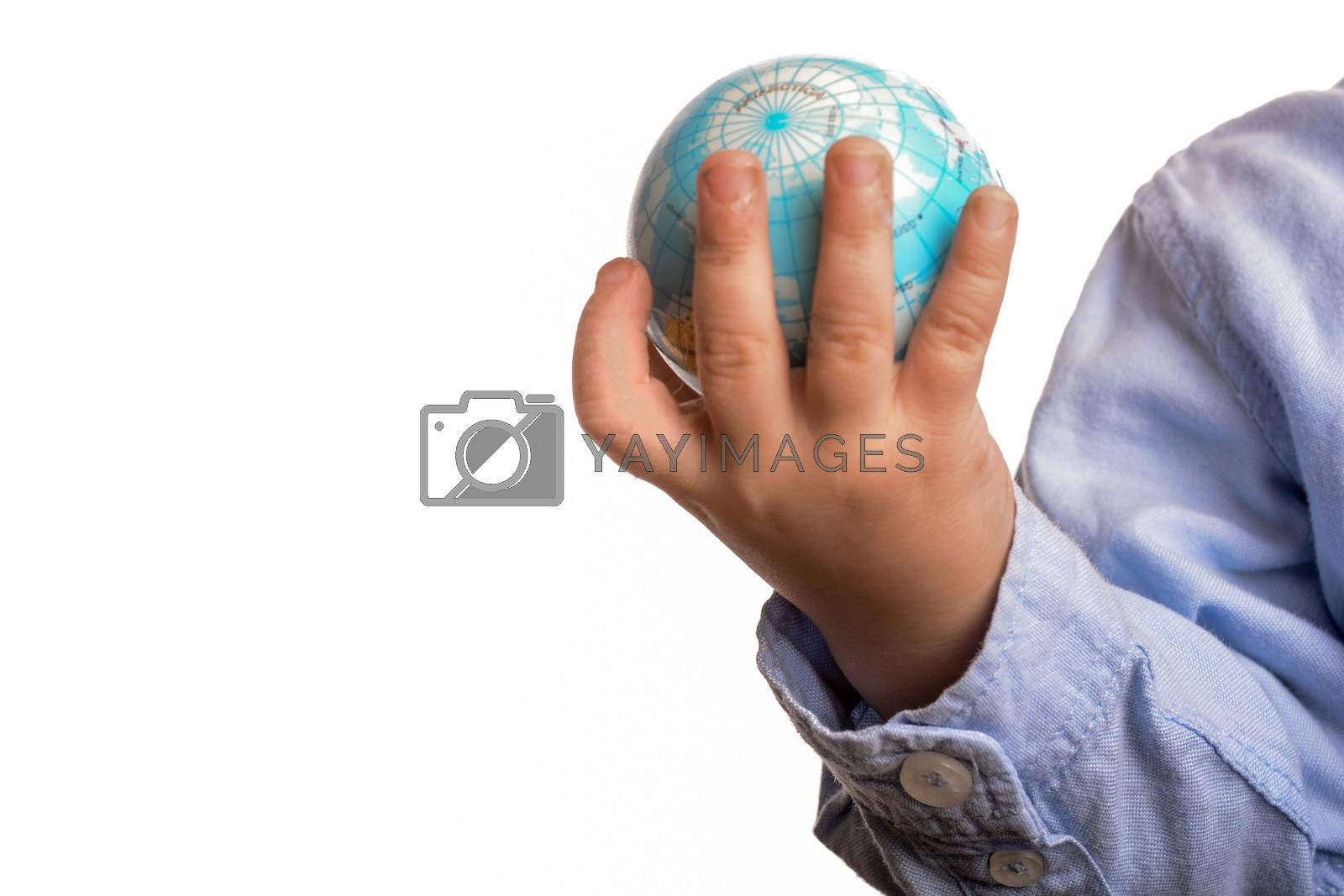 Baby with blue shirt holding a small globe in hand on white background