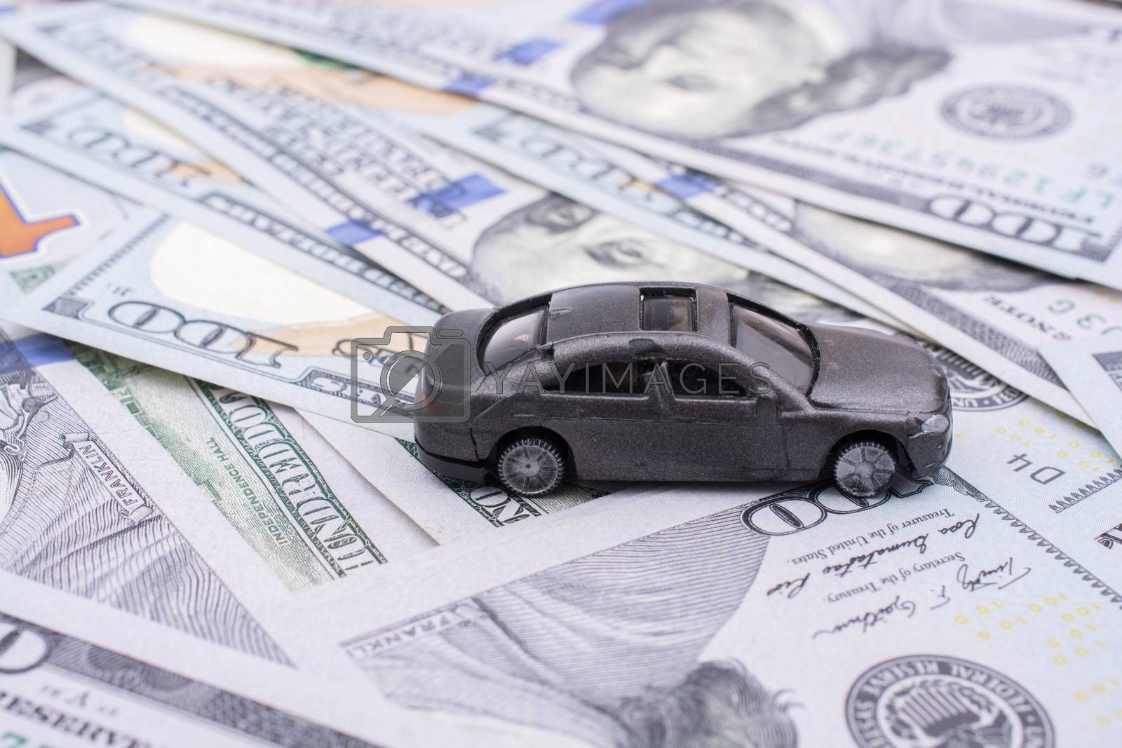 Model car placed US dollar banknotes spread on ground