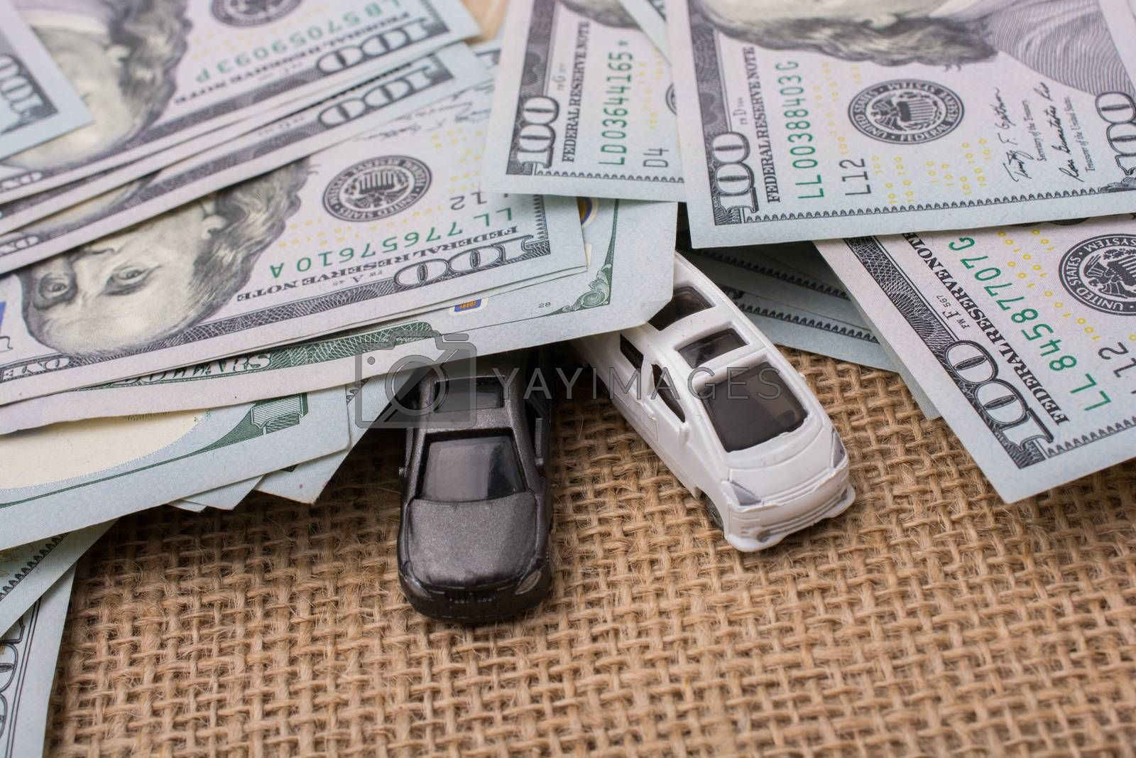 Model cars covered by US dollar banknotes spread on ground