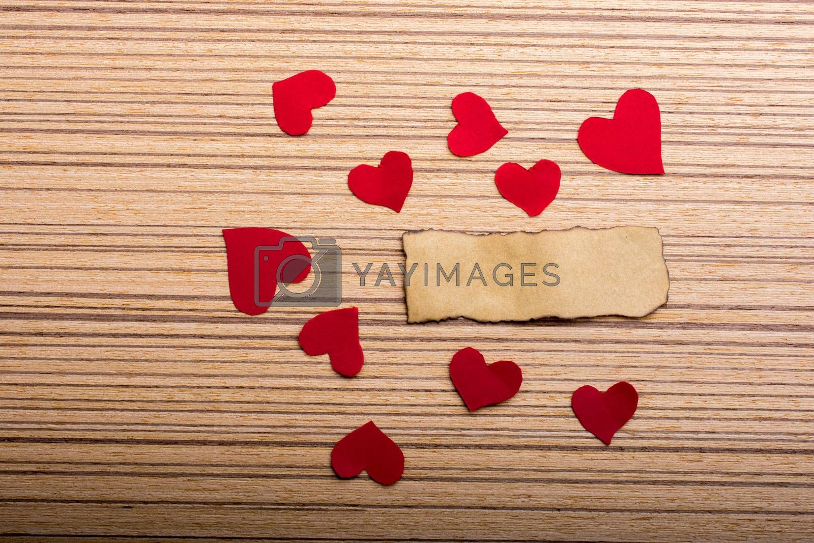 Red color paper hearts a yellow torn paper