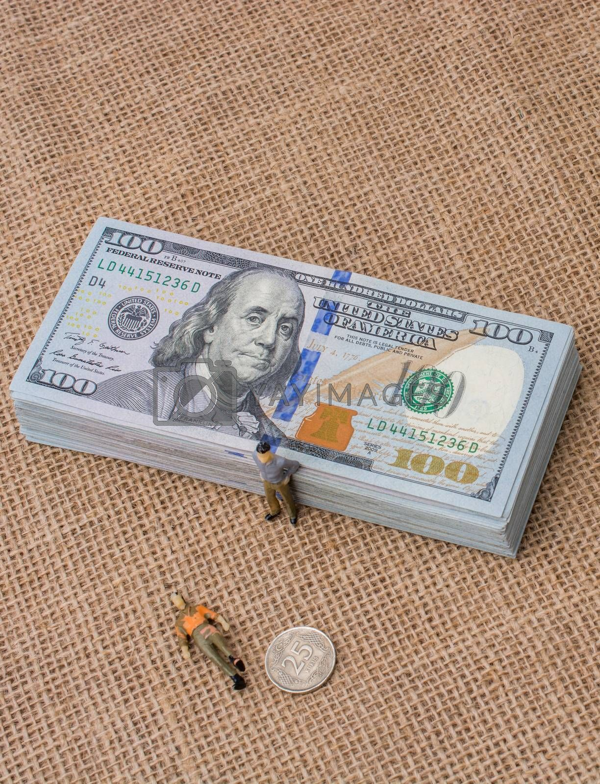 Men figurines found beside the bundle of US dollar banknote