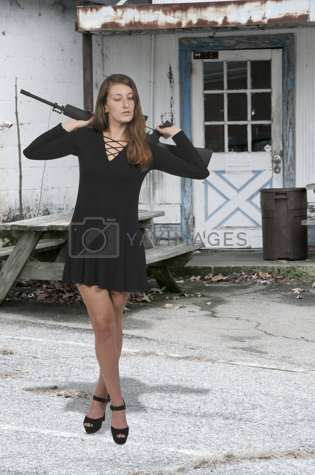 Beautiful young woman with an automatic rifle