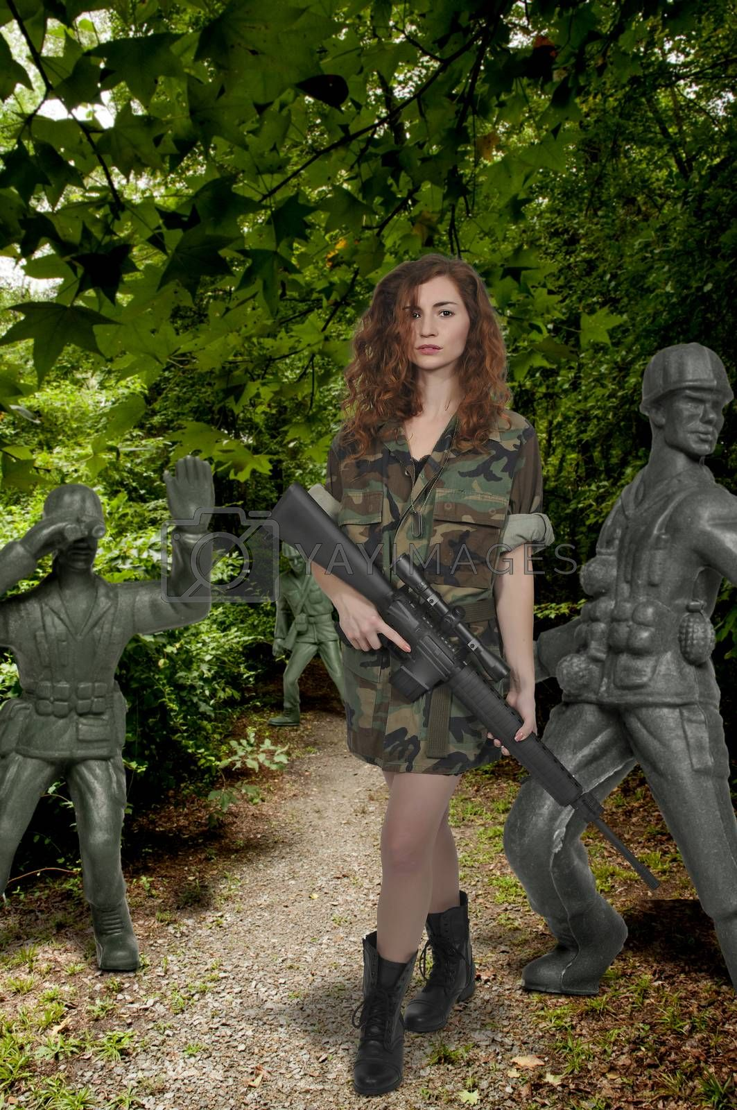 Beautiful young woman soldier with a M16 rifle and plastic toy army men