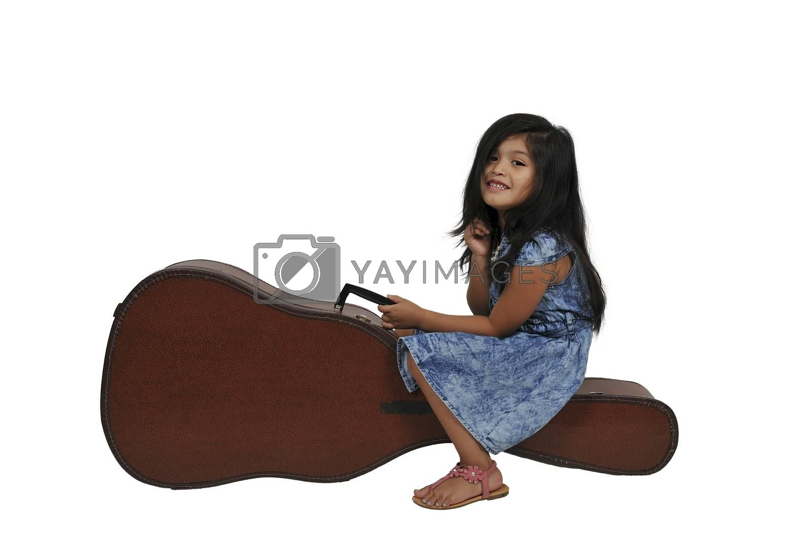 Little girl sitting on a acoustic guitar case