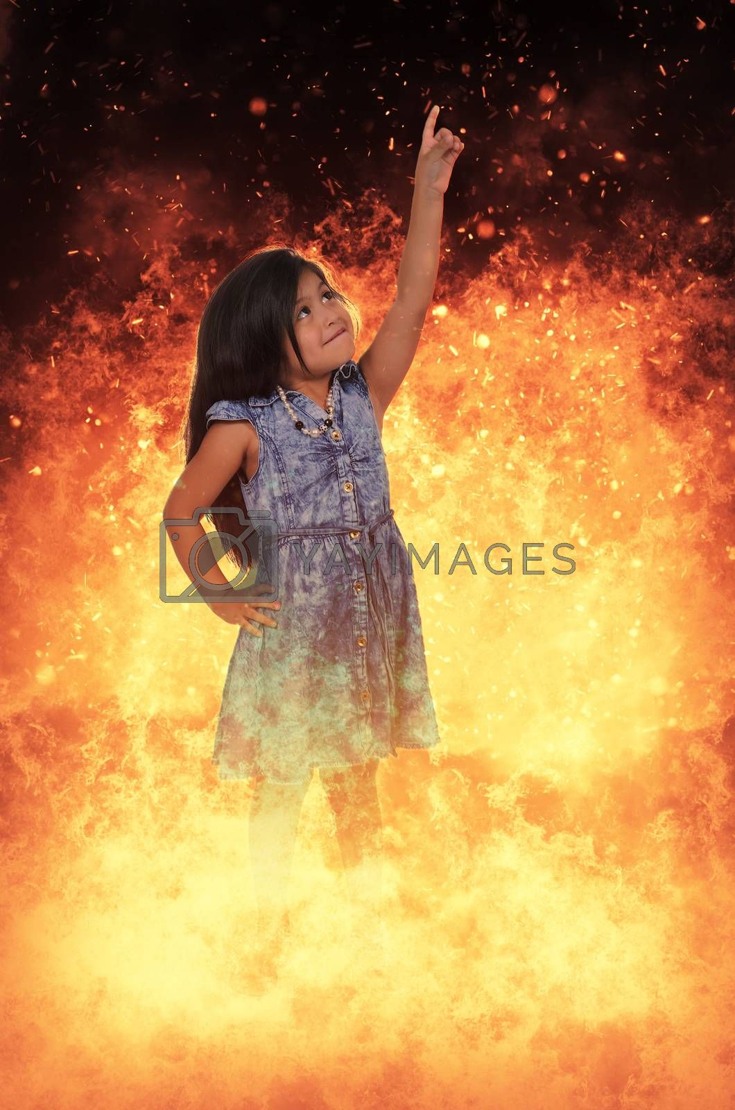 Beautiful little girl standing in the midst of a fire