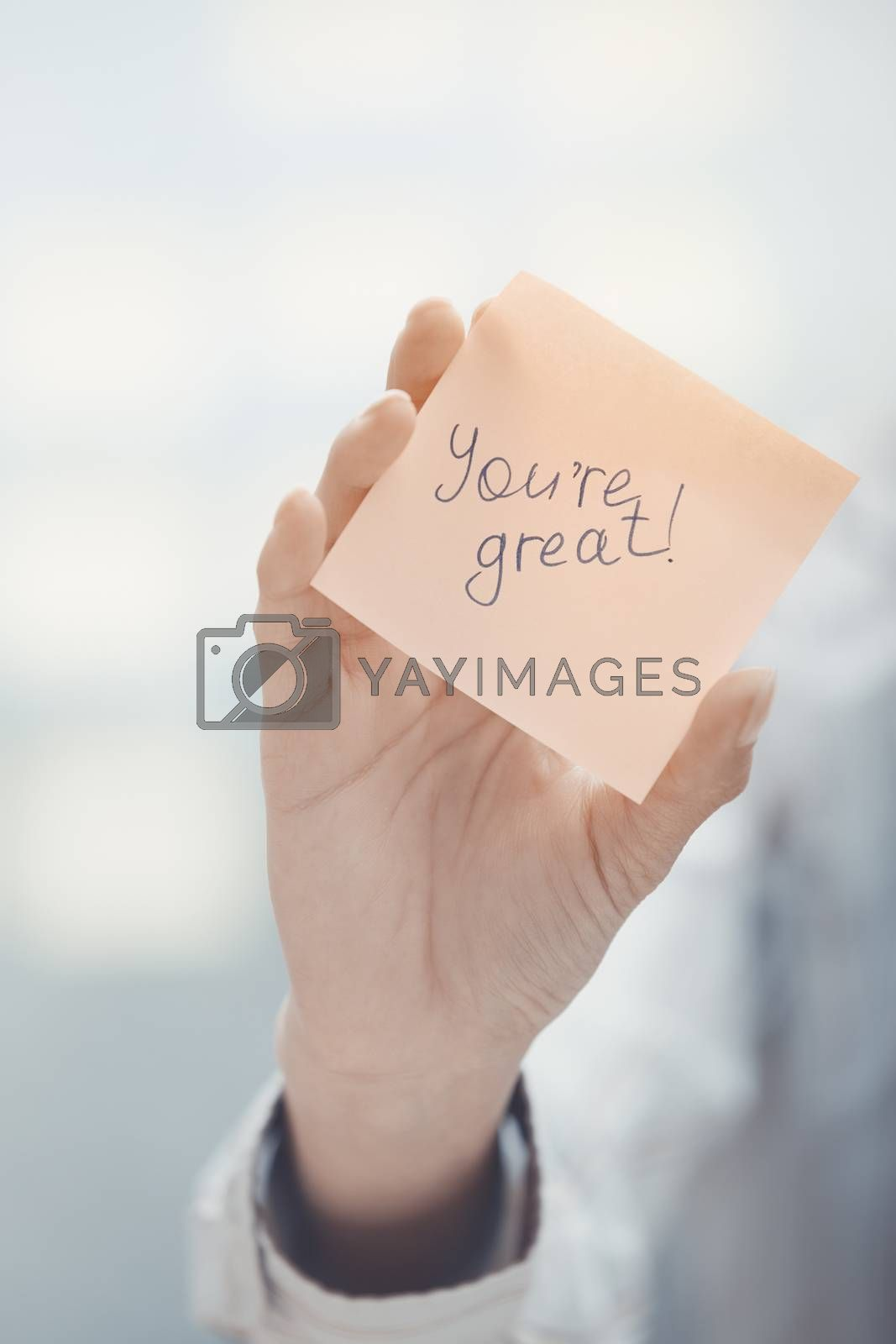 Woman holding sticky note with You are great text