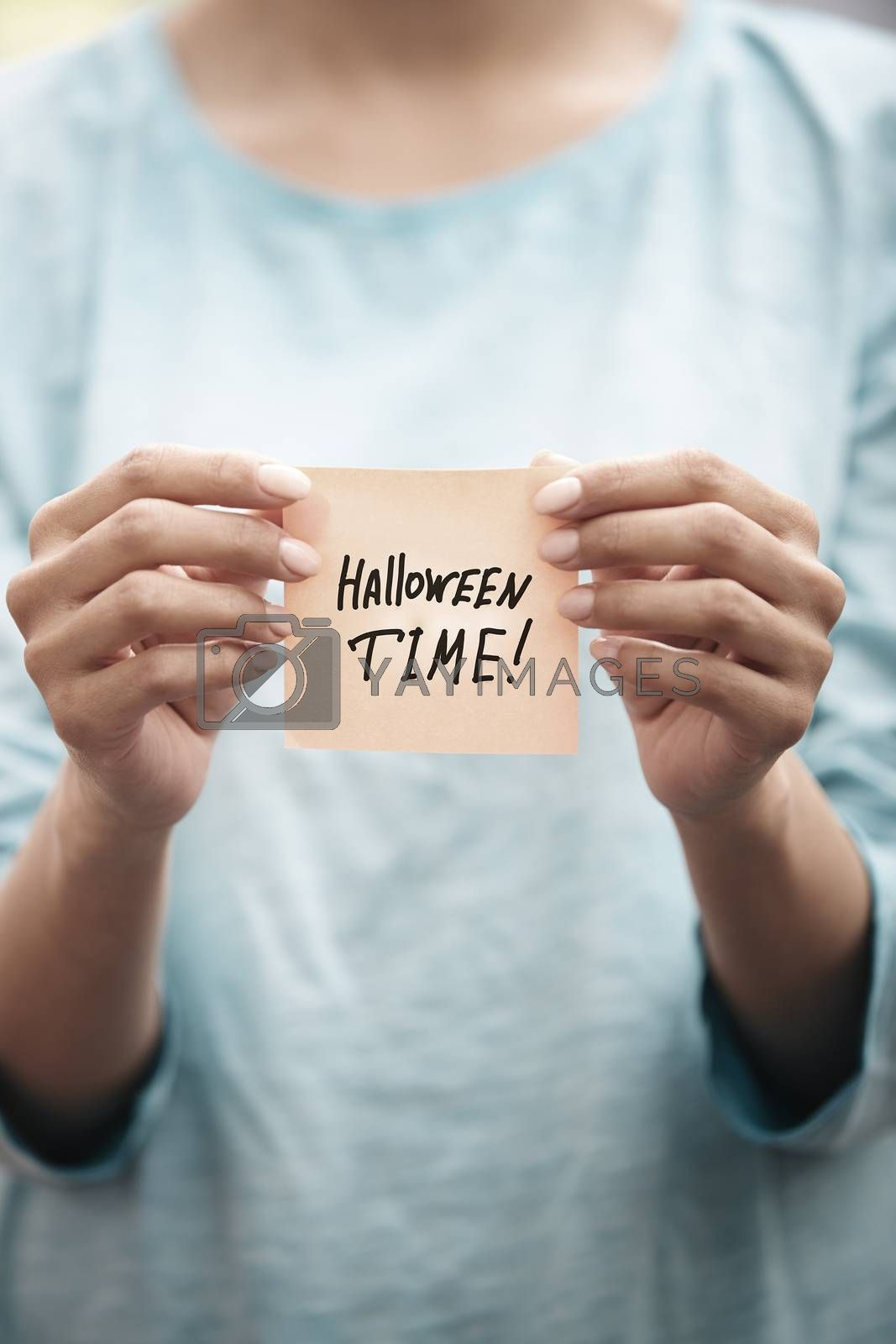 Woman holds adhesive note with Halloween time text