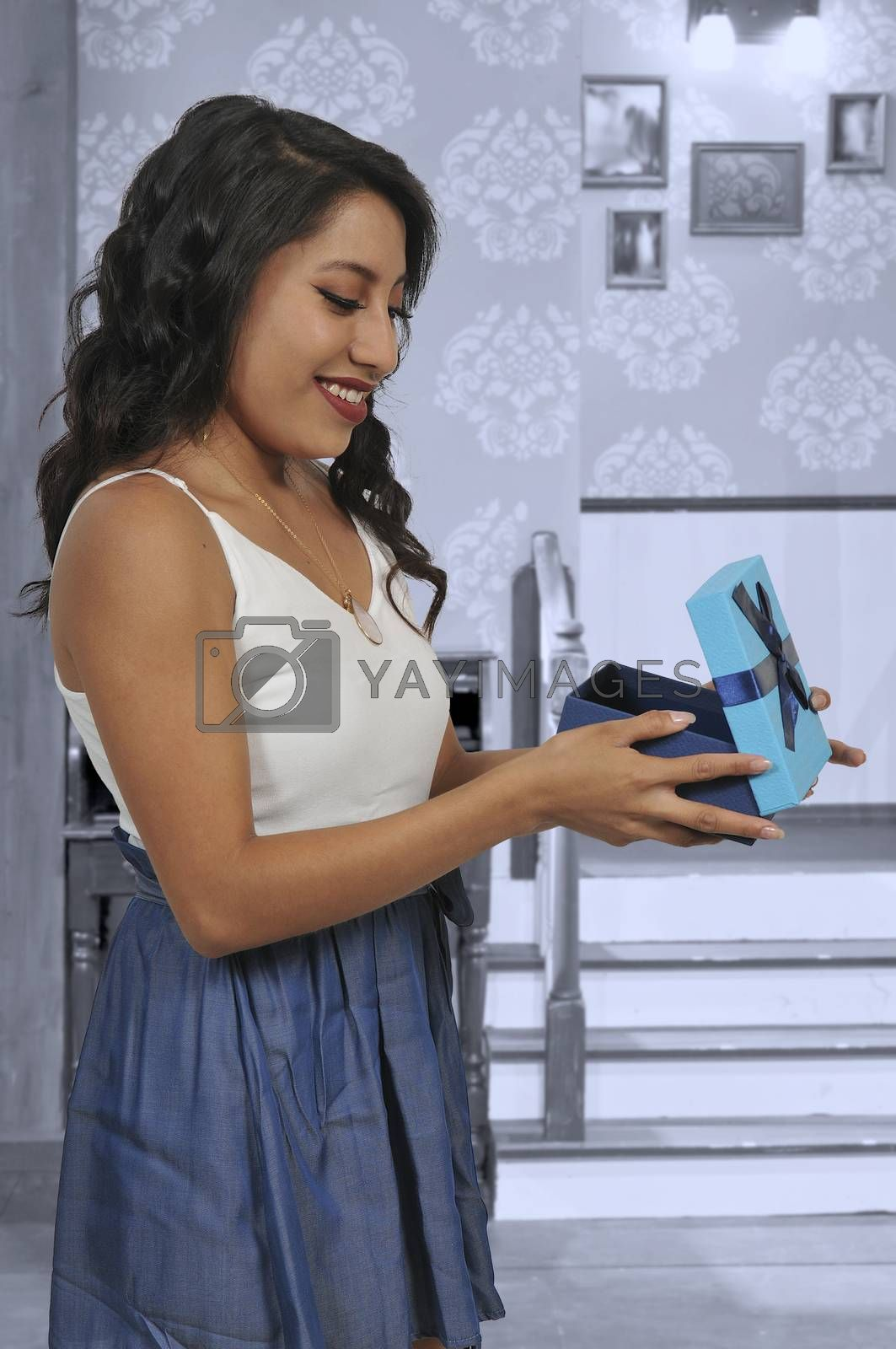 Beautiful young woman opening a gift or present