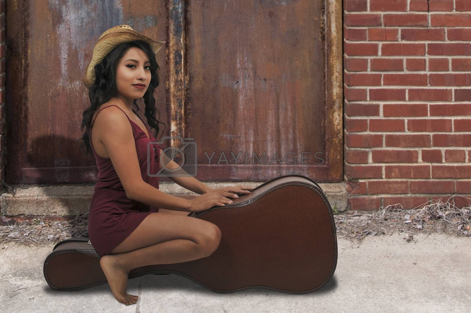 Beautiful young woman sitting on a acoustic guitar case