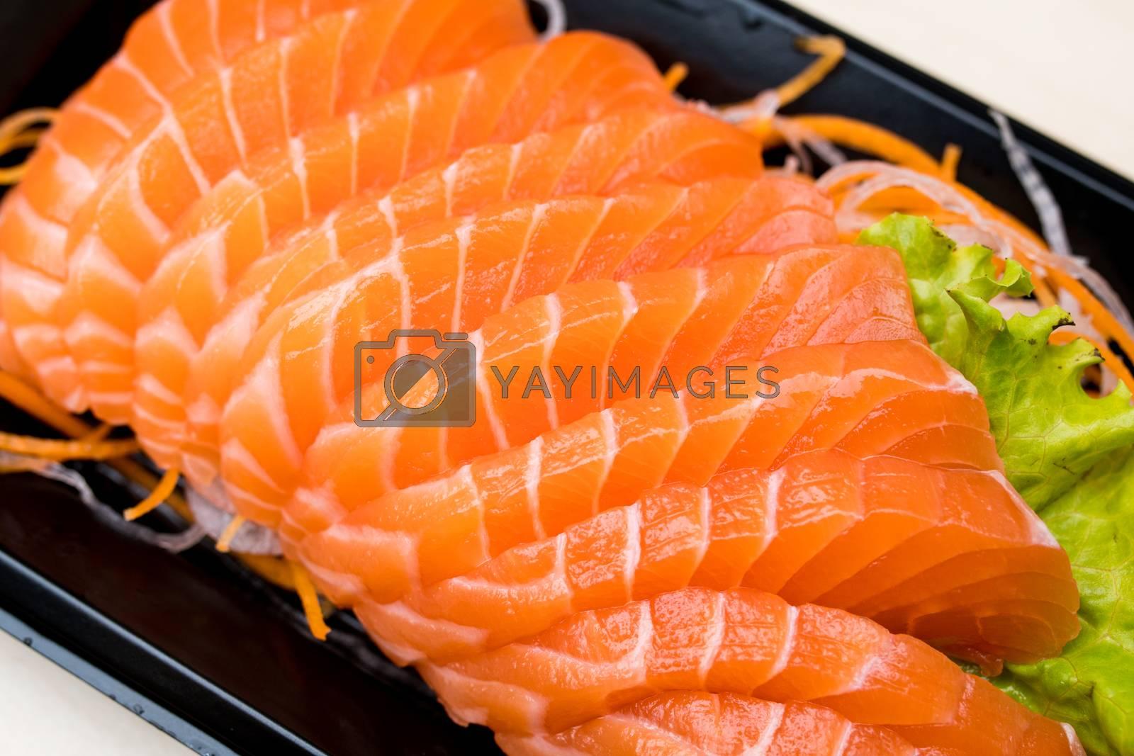 Royalty free image of sliced salmon sashimi on black plate by antpkr