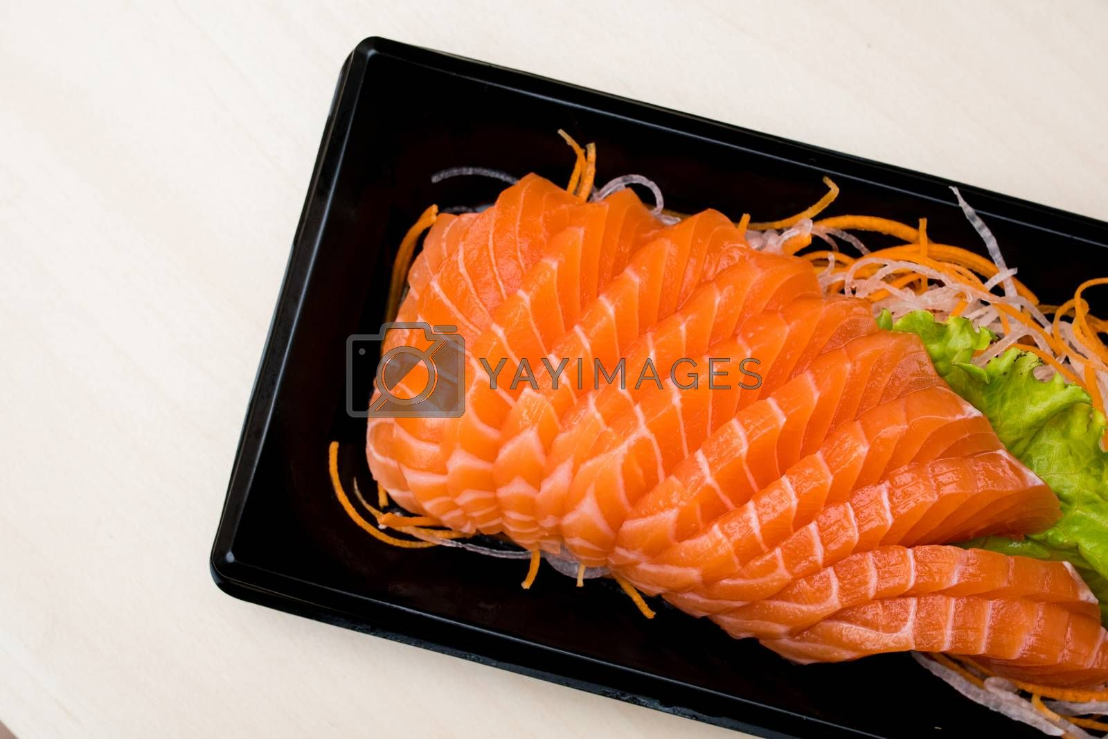 sliced salmon sashimi on black plate